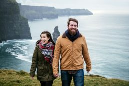 engaged couple walking along the Cliffs of Moher Ireland