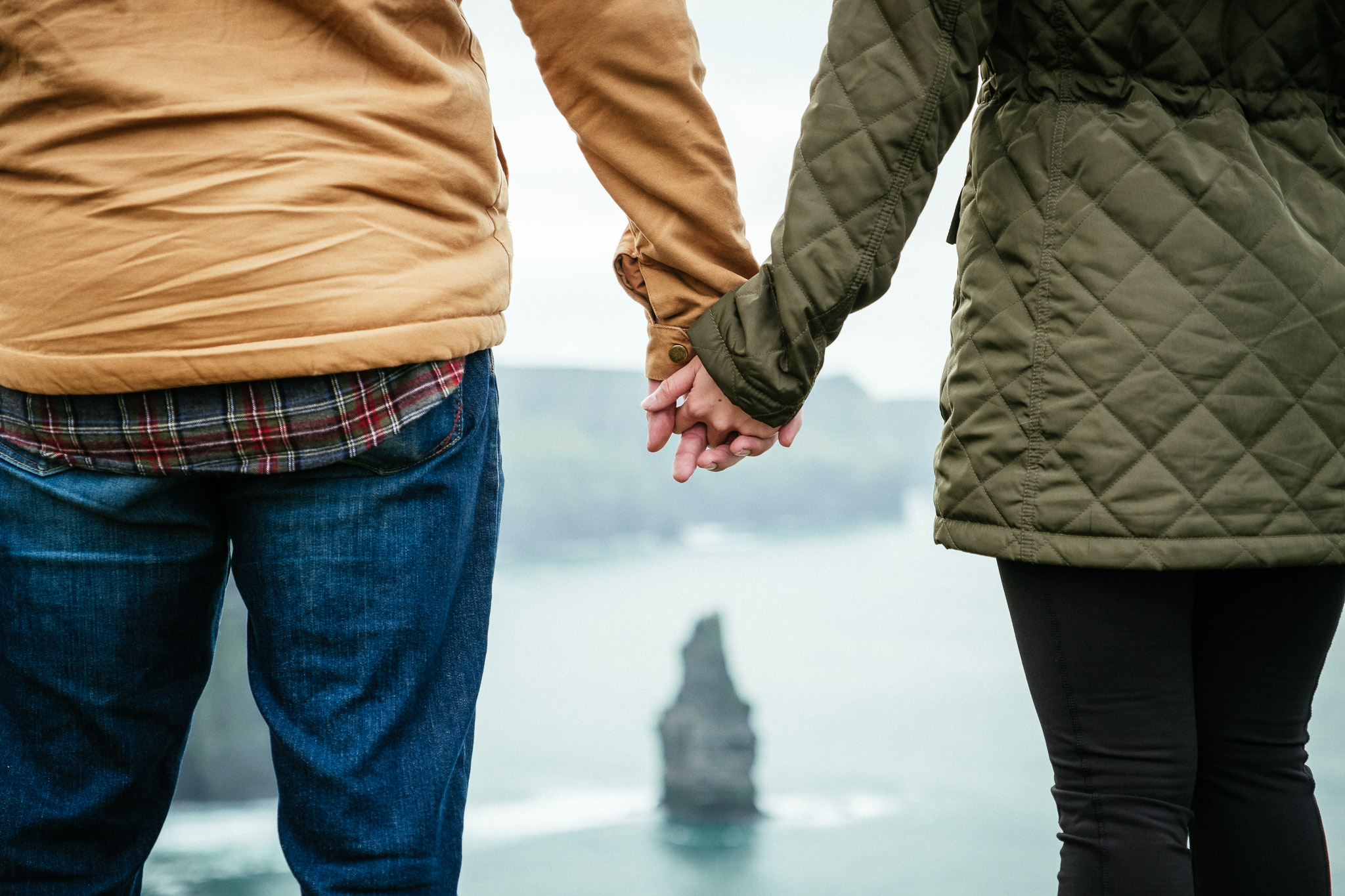 engaged couple holding hands at the Cliffs of Moher Ireland