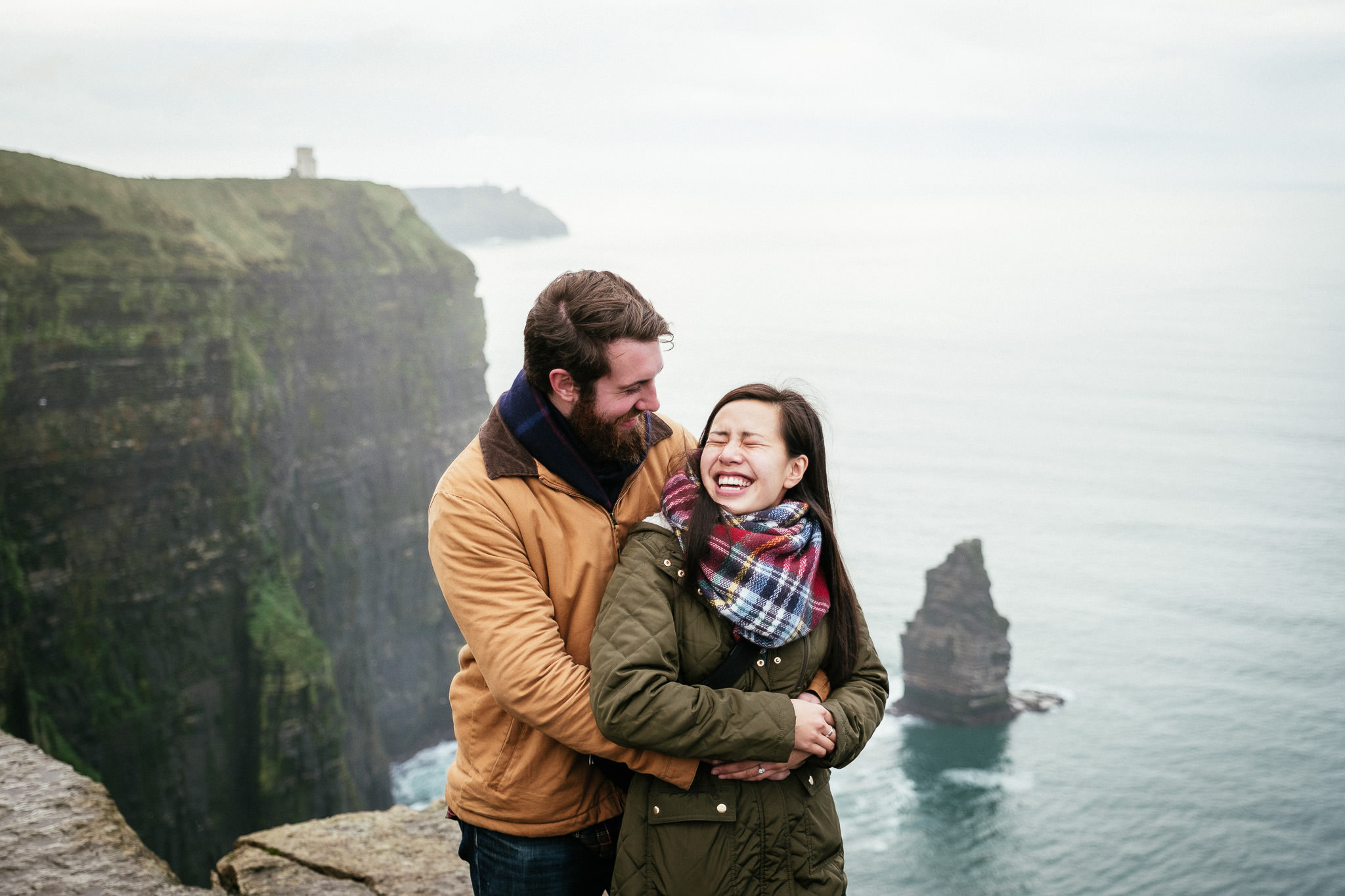 engaged couple hugging at the Cliffs of Moher with a sea stack in the background