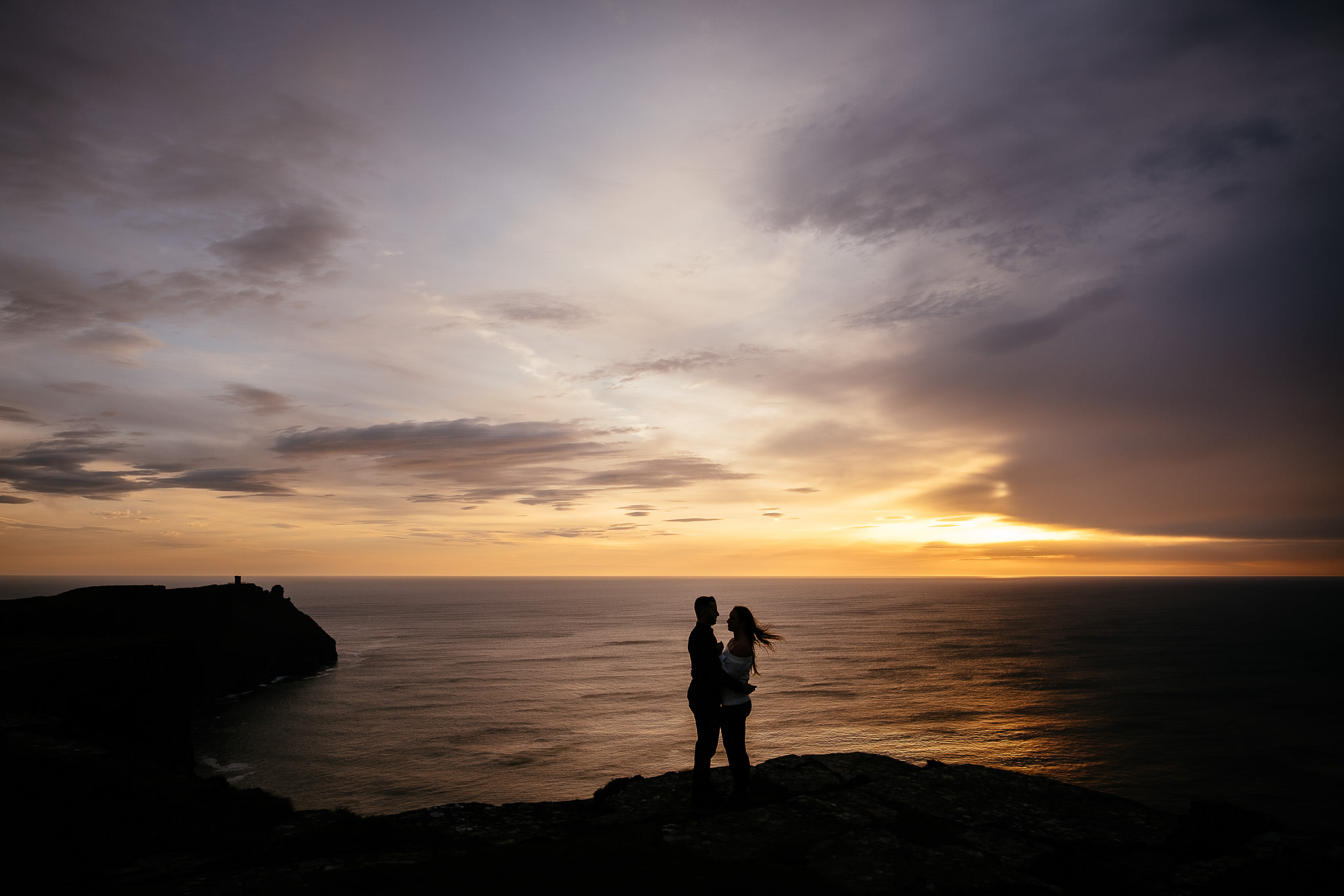 engaged couple at the Cliffs of Moher Ireland with the sun setting over the ocean