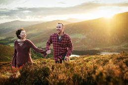 guy and girl walking through a mountain with the sun setting behind them at the best location in Ireland for an engagement shoot or elopement