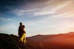 engaged couple at top of mountain in lreland watching the sun set