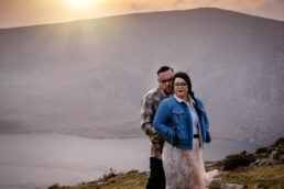 engaged couple standing together on a mountain top at sunset