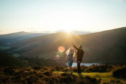 engaged couple dancing at top of mountain in lreland watching the sun set