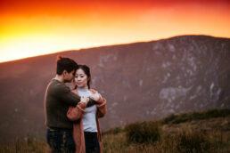 engaged couple embracing at sunset
