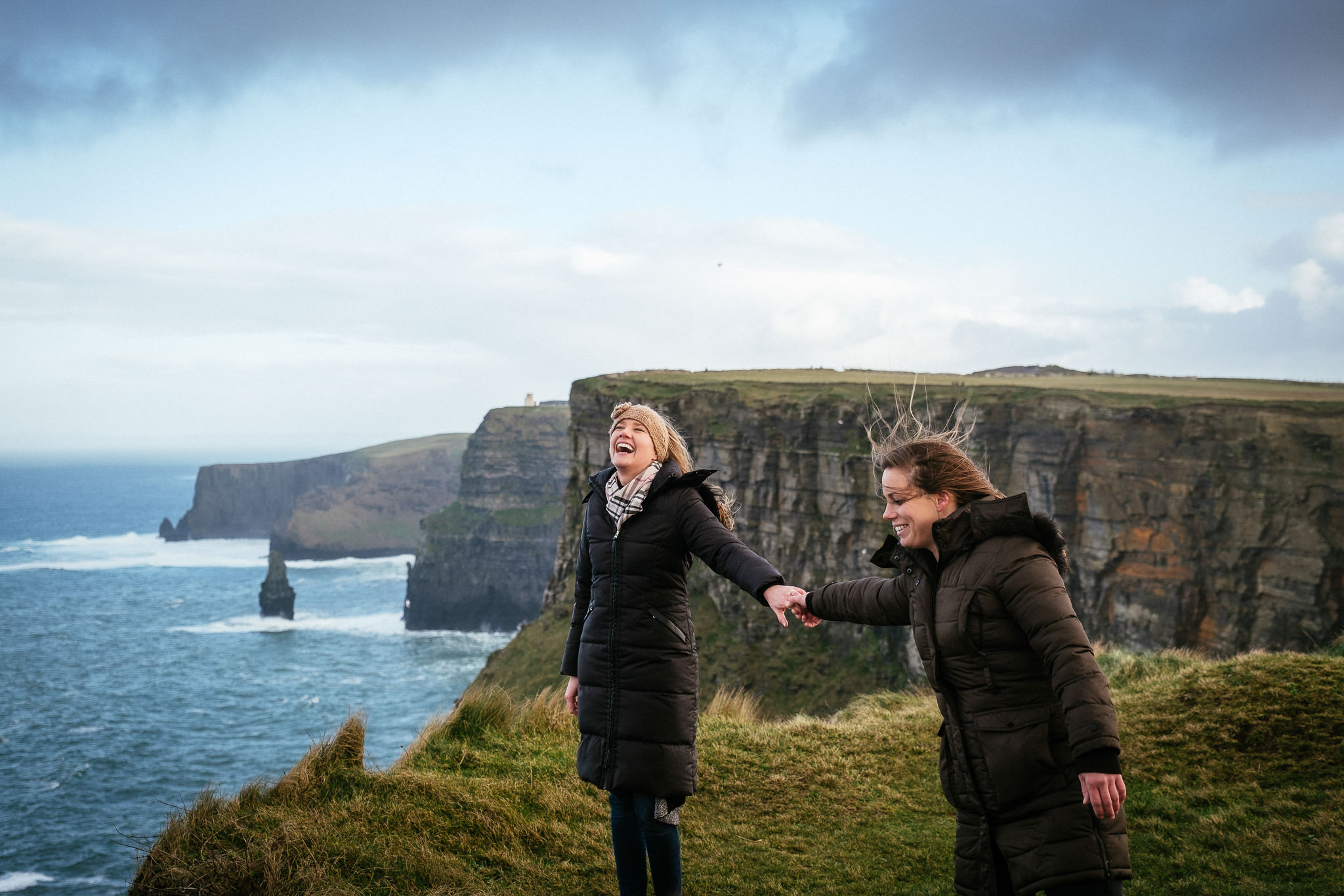 LGBT couple laughing at the Cliffs of Moher Ireland