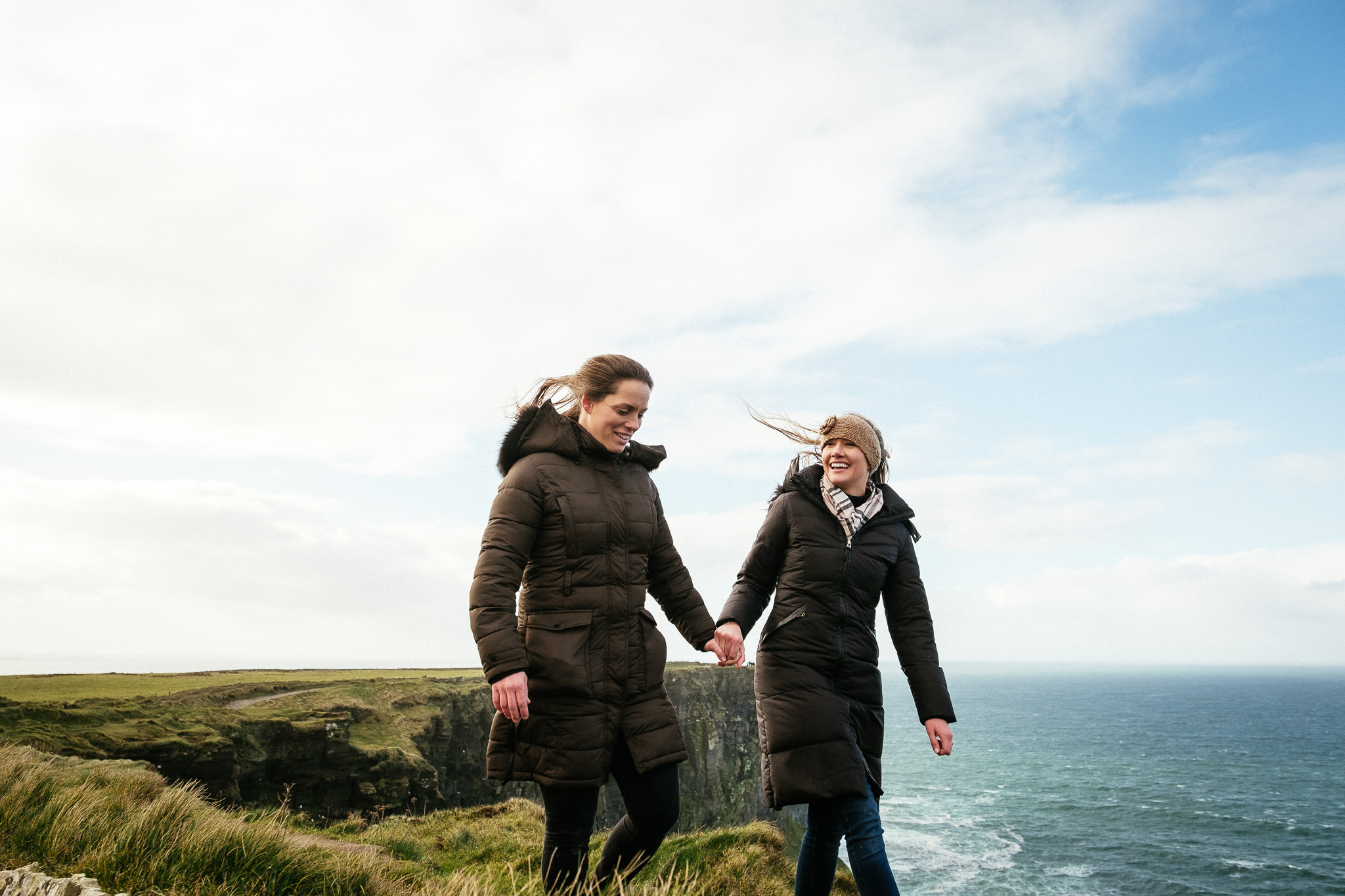 lesbian couple holding hands at the Cliffs of Moher Ireland