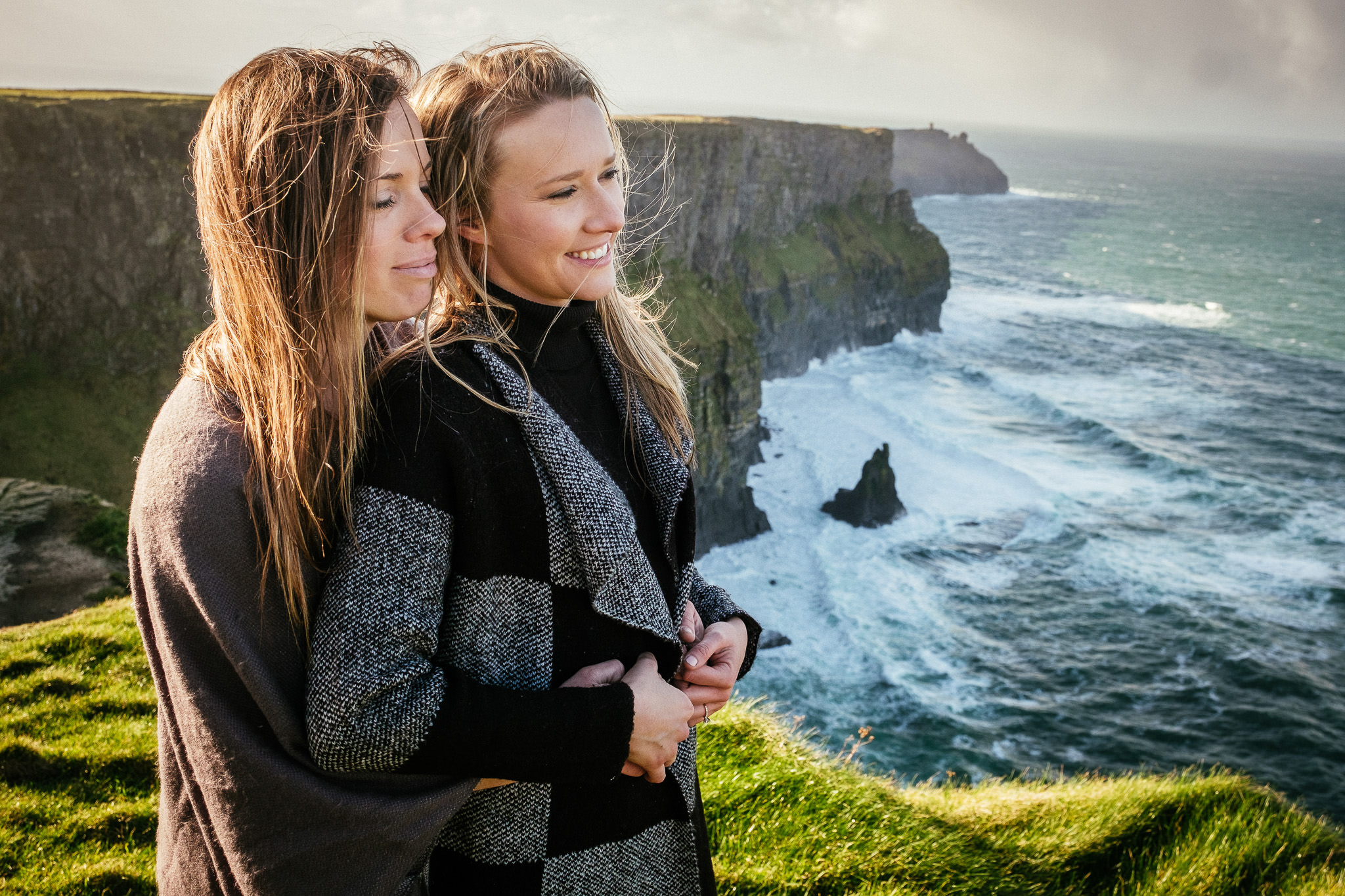 LGBT couple embracing on the cliffs of moher
