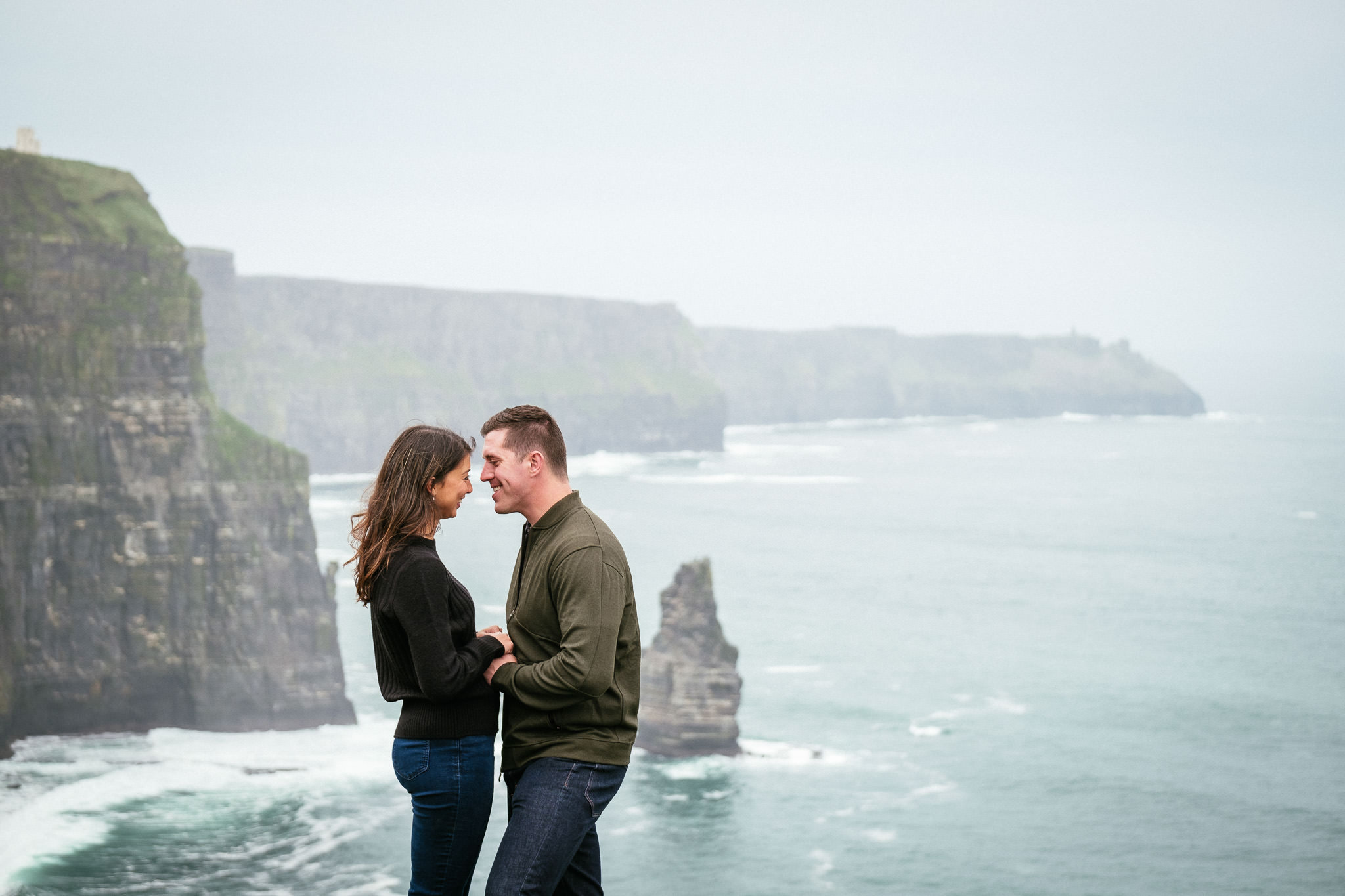 engaged couple embracing at the Cliffs of Moher Ireland