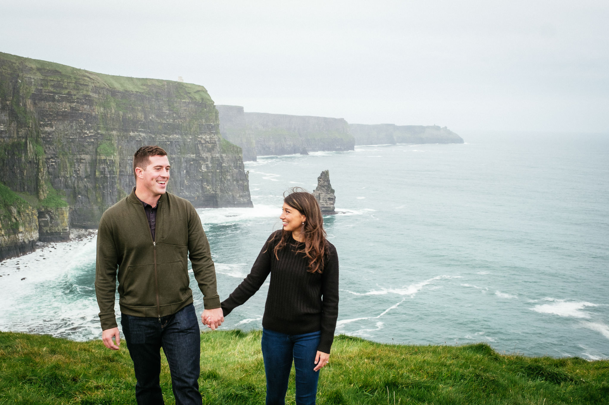 engaged couple holding hands during their engagement shoot at the Cliffs of Moher