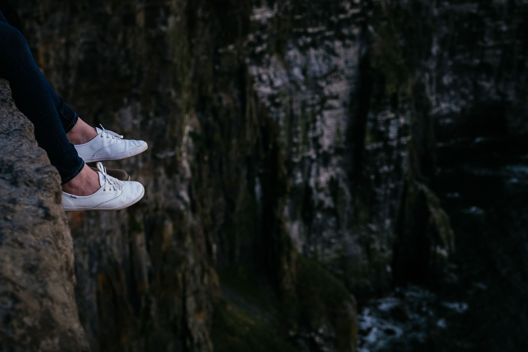 feet dangling off cliff at the Cliffs of Moher Ireland