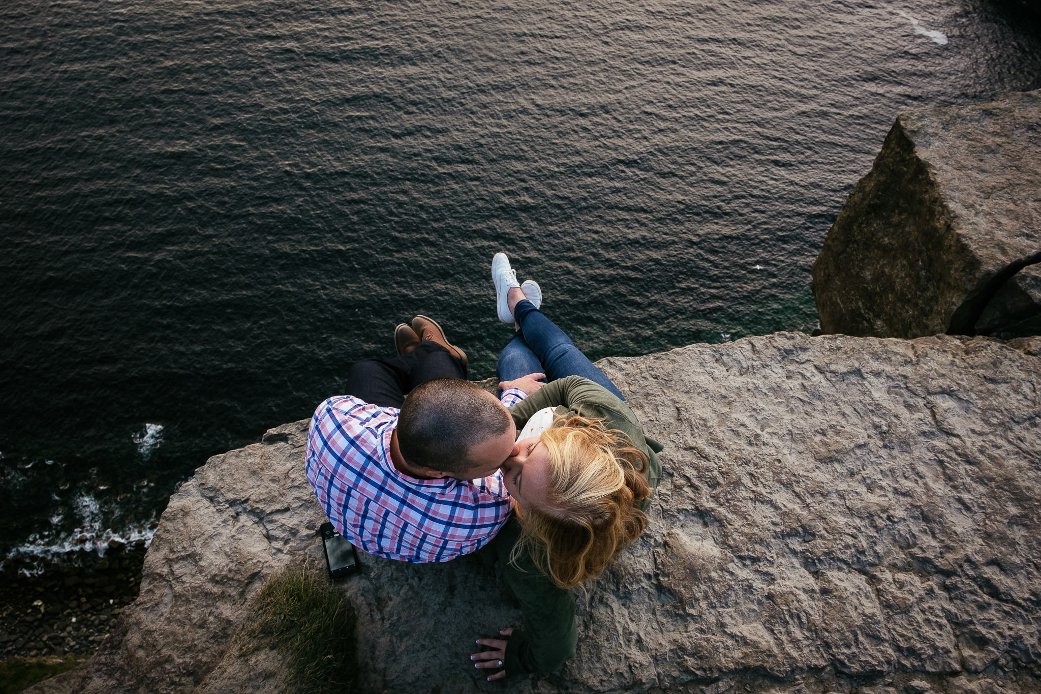 engaged couple sitting at the ende of the Cliffs of Moher Ireland