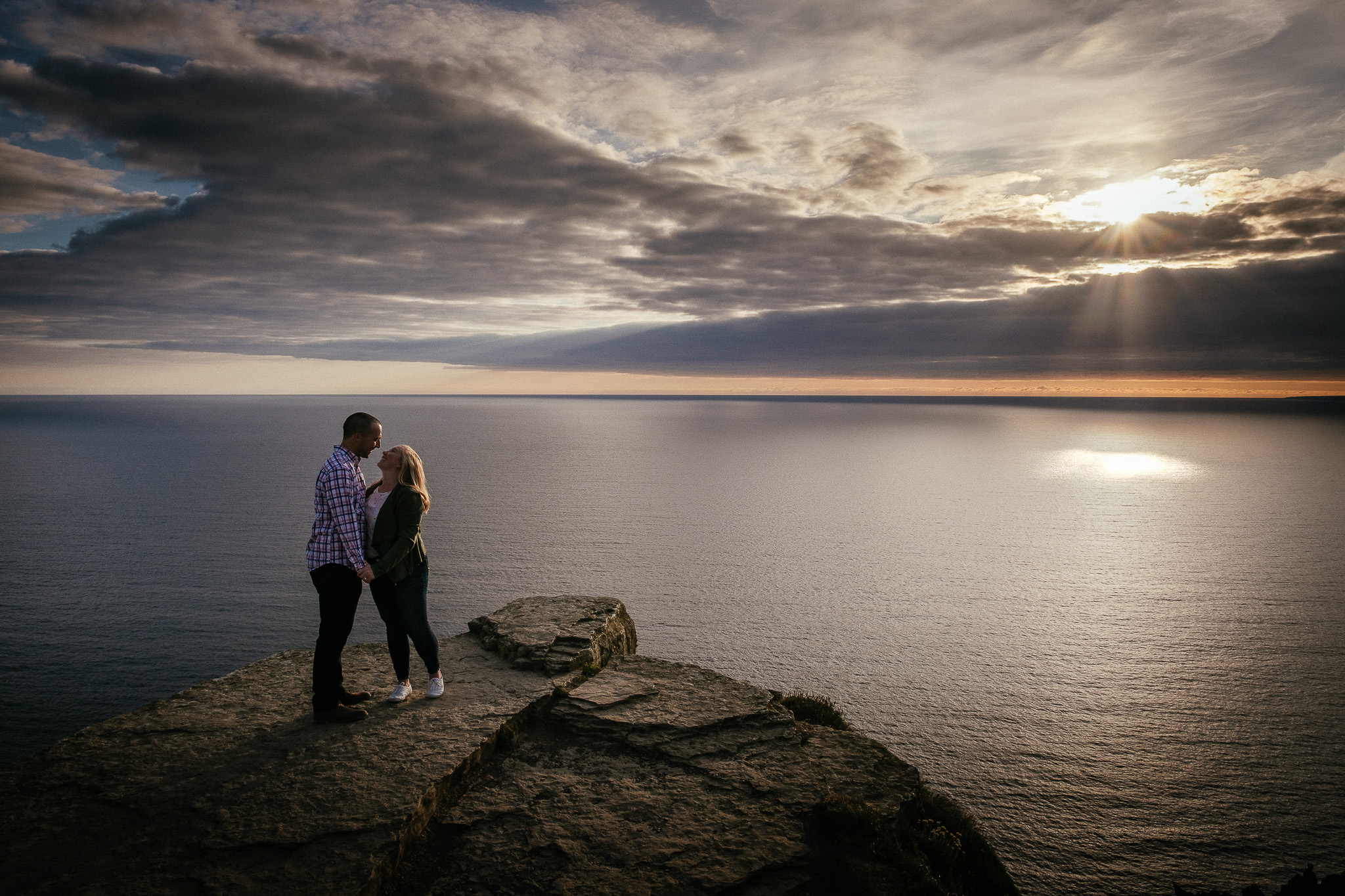 engaged couple kissing at the Cliffs of Moher Ireland