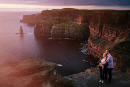 engaged couple looking at the ocean during their engagement shoots at the Cliffs of Moher