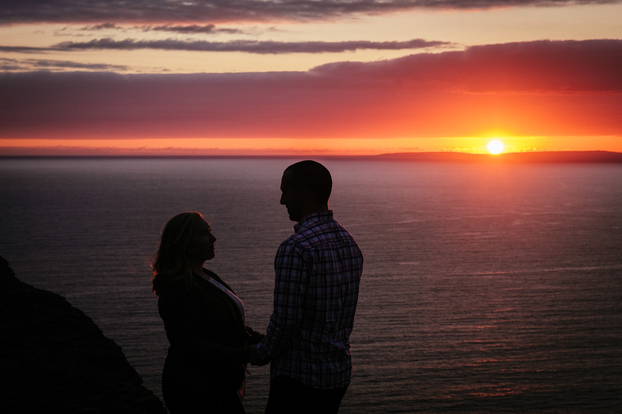 engaged couple with the sun setting over the aran islands