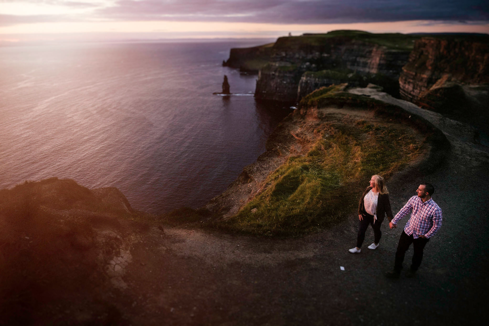 engaged couple walking along the cliffs at sunset at the Cliffs of Moher Ireland