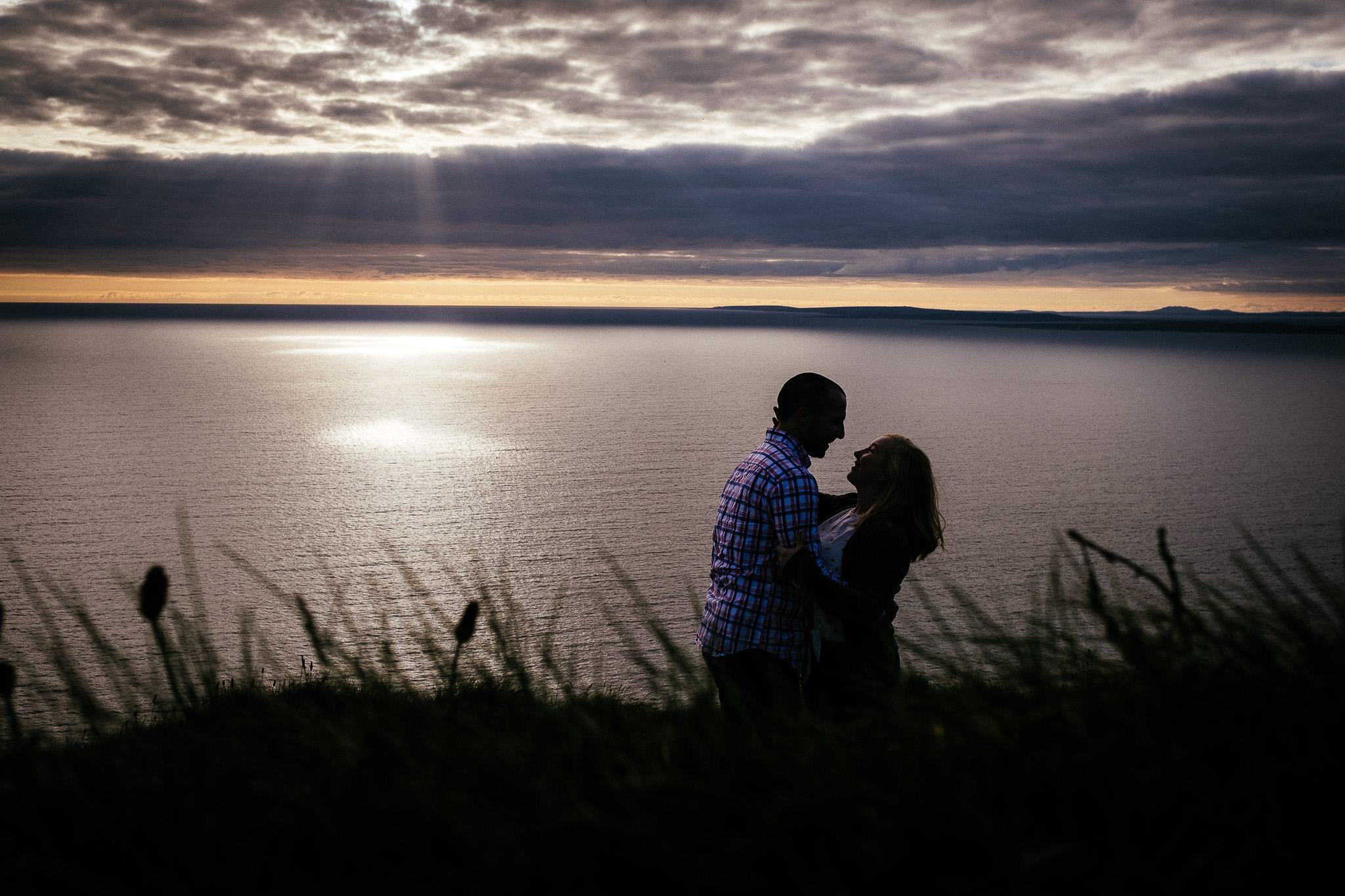 engaged couple with the sun setting at the Cliffs of Moher Ireland