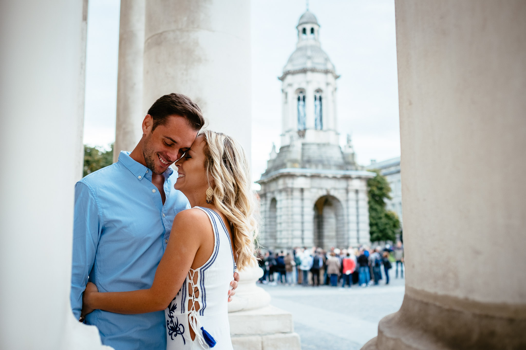 engaged couple hugging during their engagement photo session in Trinity College Dublin Ireland