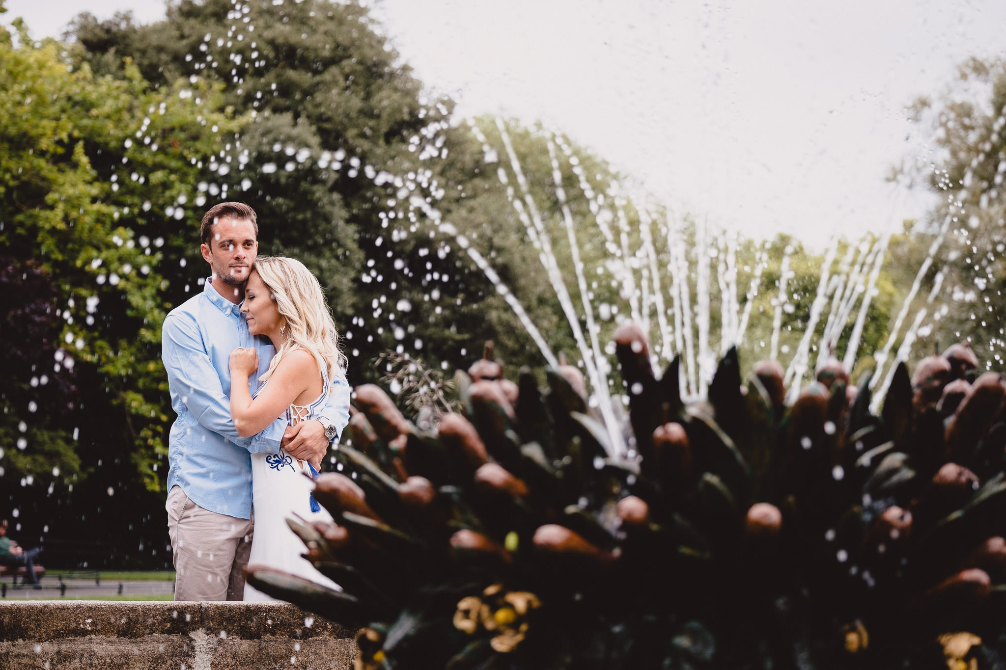 engaged couple hugging by a water fountain in St Stephens Green Park Dublin