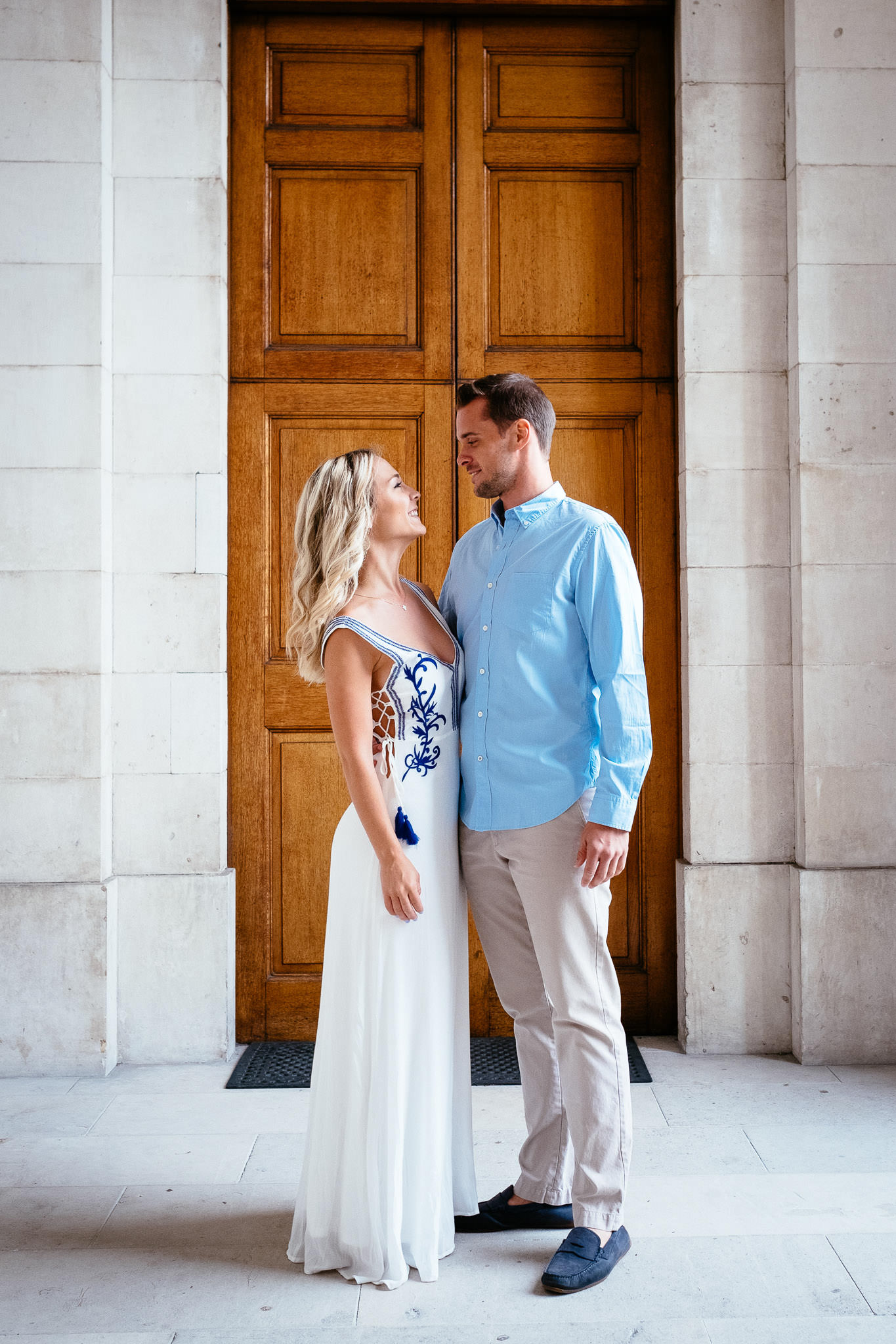engaged couple standing by church door during their engagement photo session in Trinity College Dublin Ireland