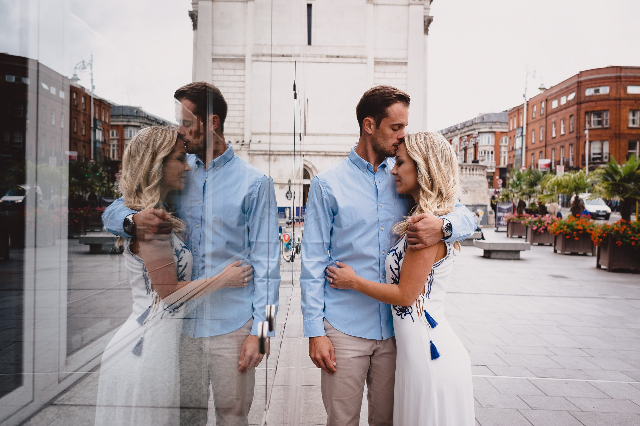 engaged couple kissing in reflection of window near City Hall in Dublin
