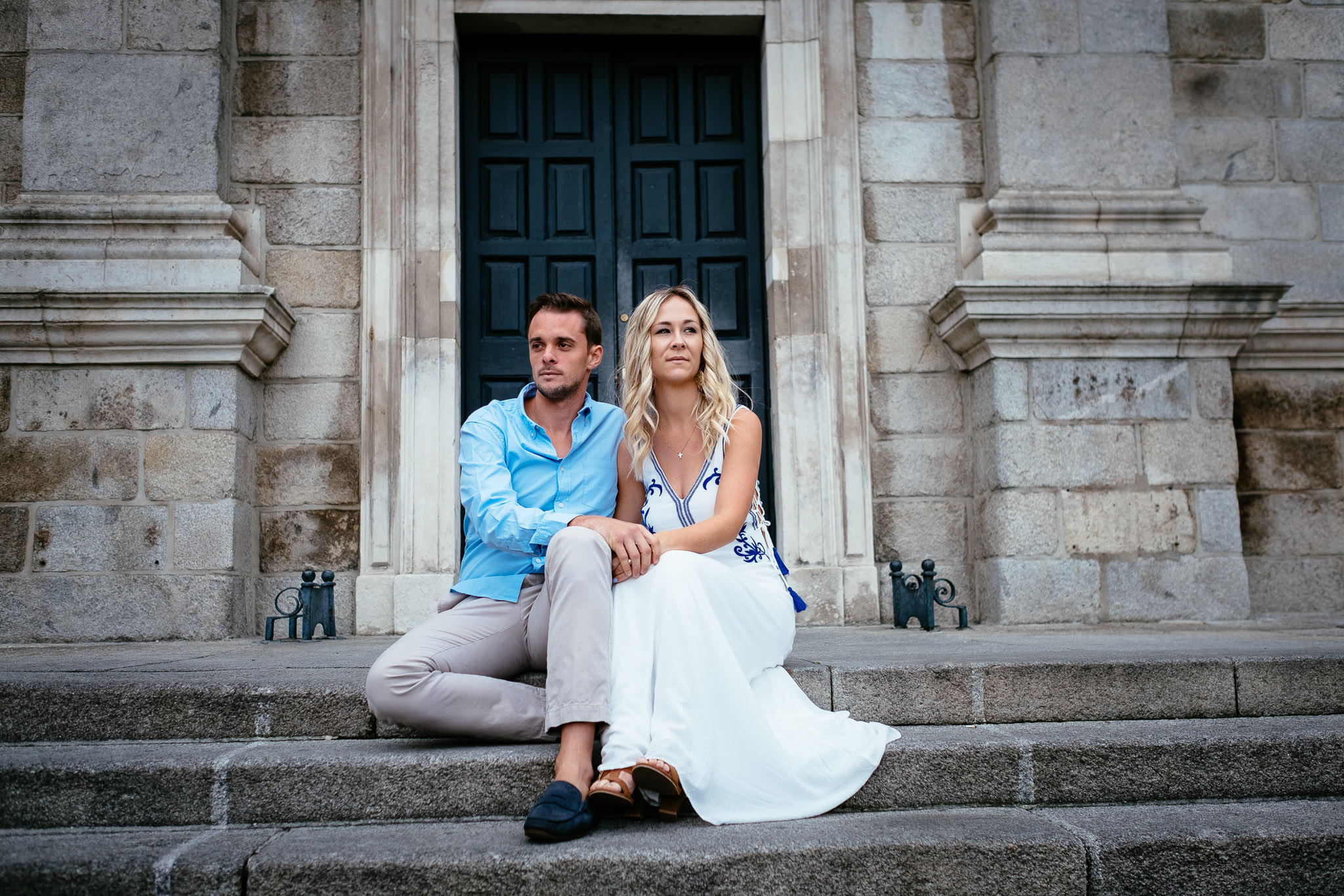 engaged US couple sitting on steps during their engagement photo session in Trinity College Dublin Ireland