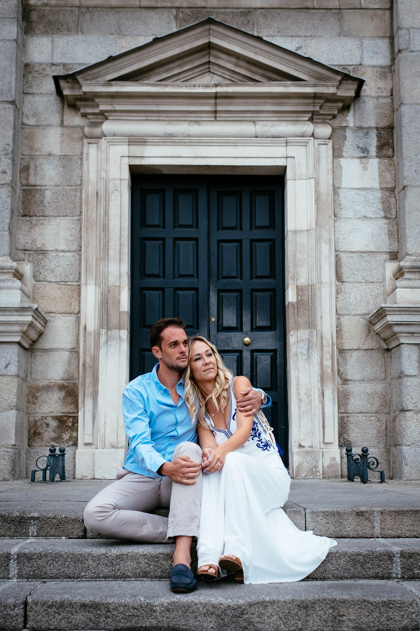 engaged guy and girl sitting by doorway during their engagement photo session in Trinity College Dublin Ireland
