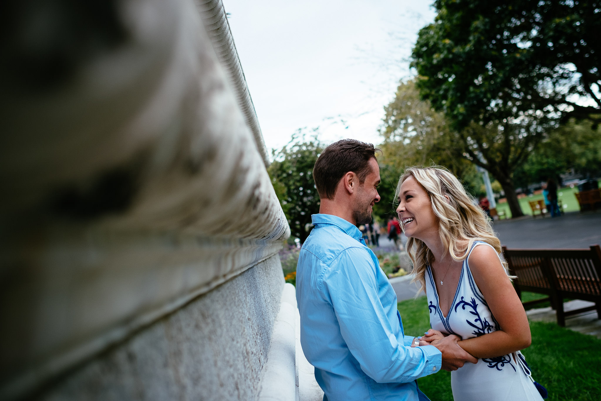 engaged hetrosexual couple laughing and standingg by a wall during their engagement photo session in Trinity College Dublin Ireland