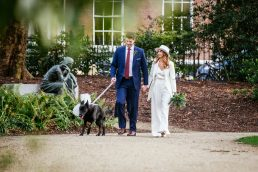 bride and groom walking their dog through Merrion Park Dublin after their Dublin registry office wedding