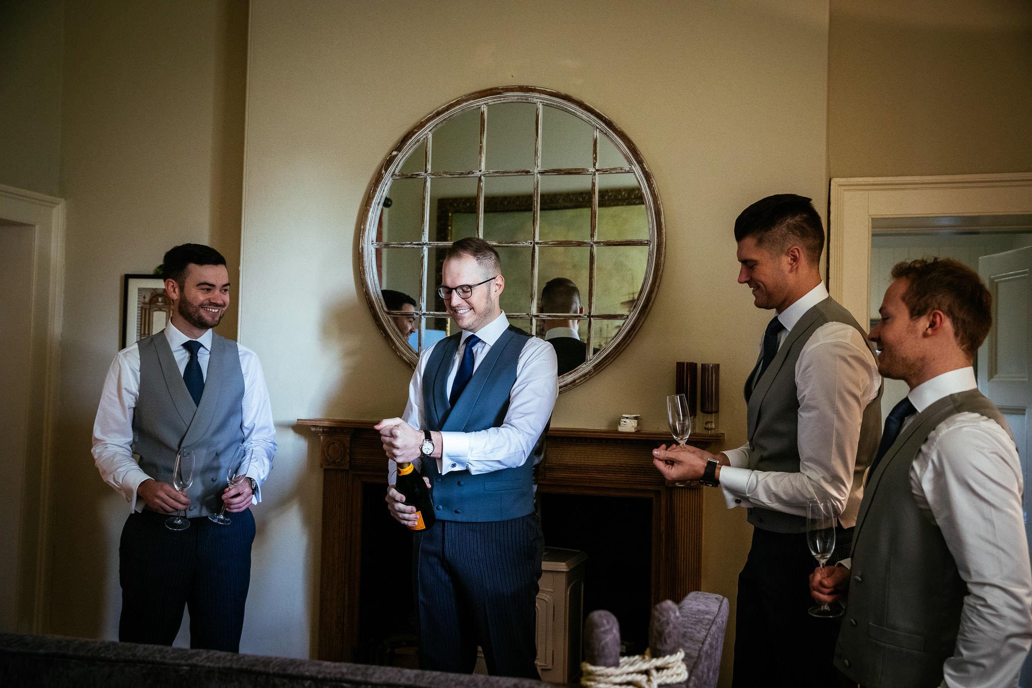 groom opening champagne at loughcrew lodge wedding