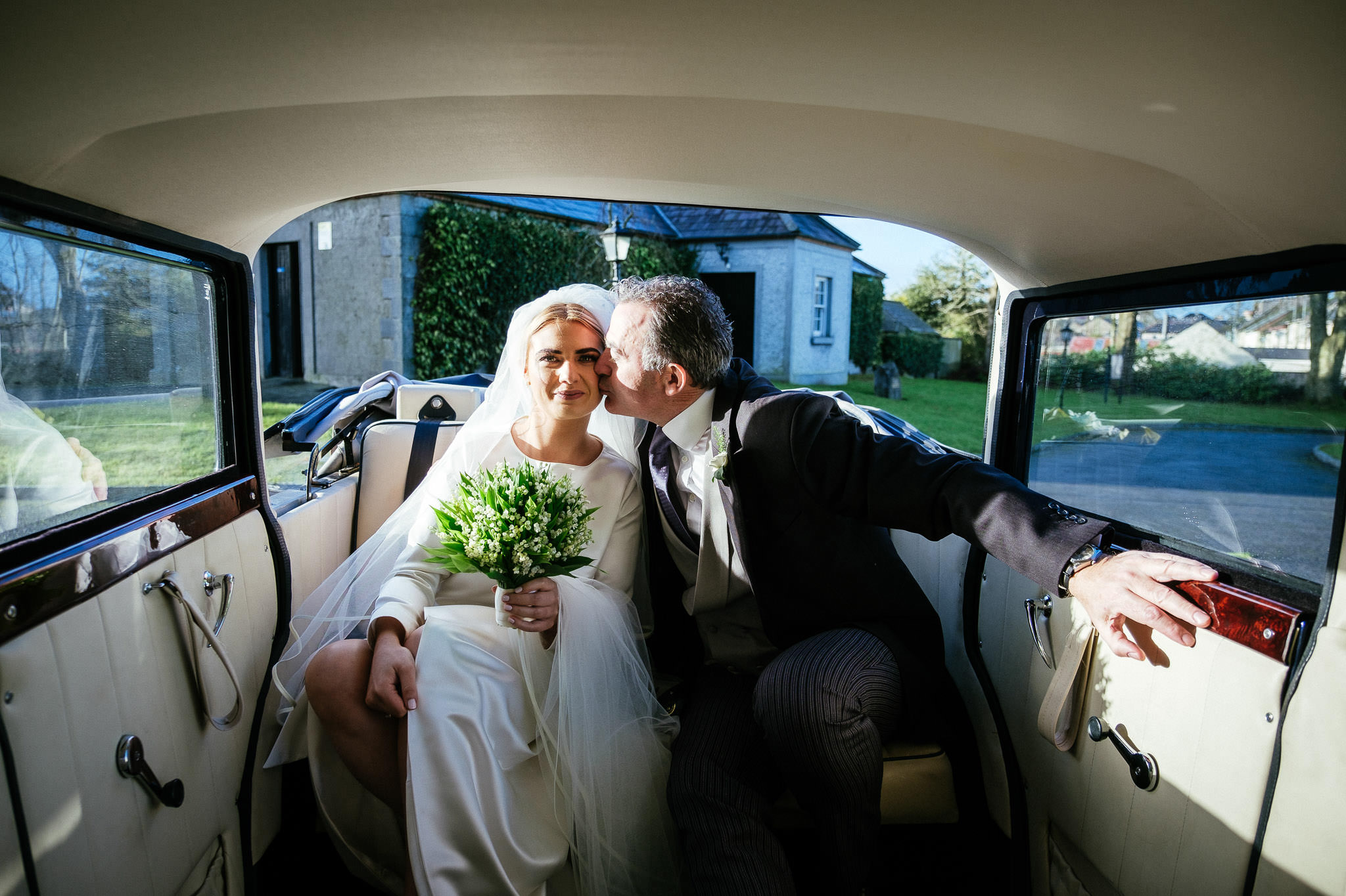 bride getting a kiss from her father in back of wedding car