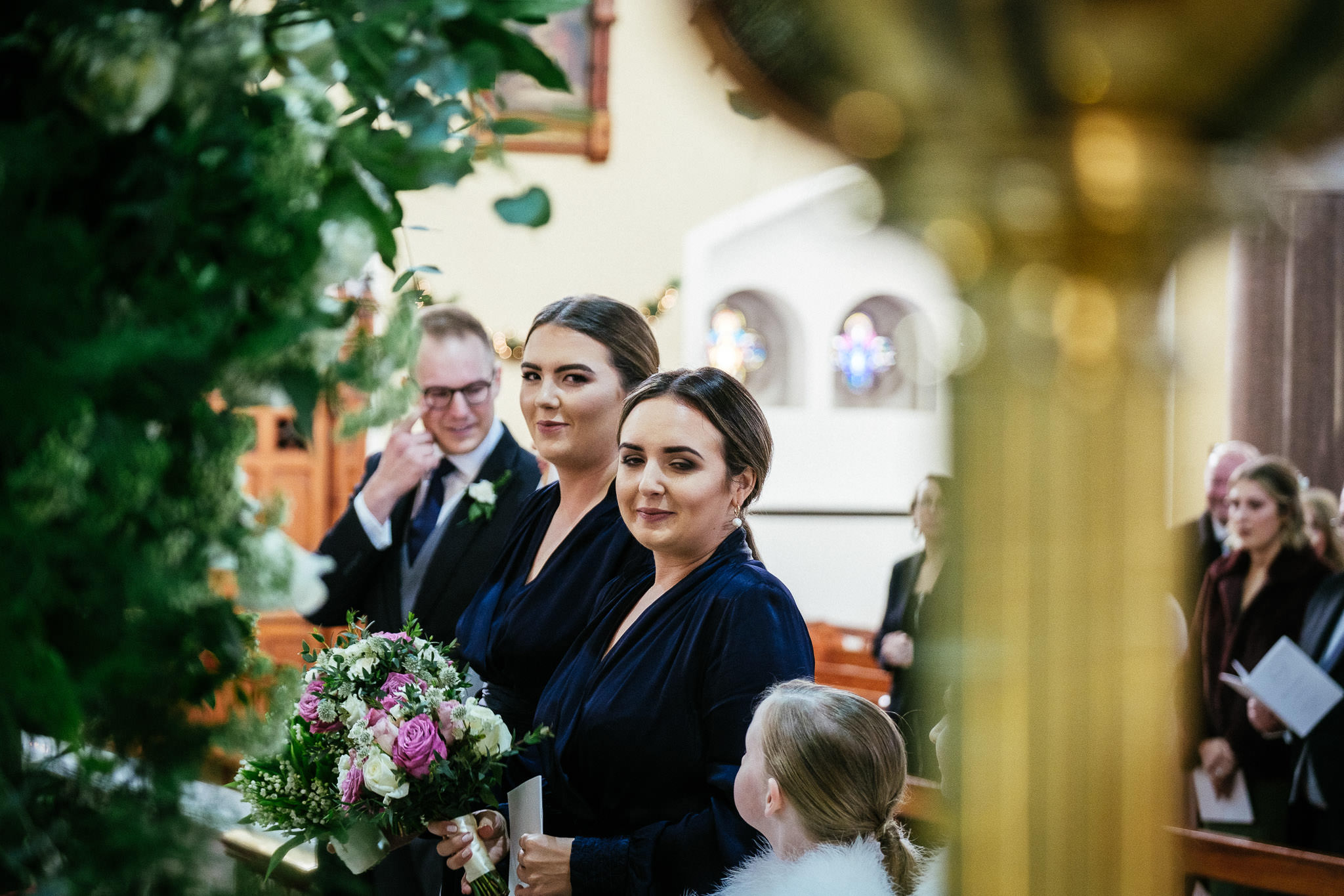 bridesmaid looking at bride during wedding ceremony at St Brigid's Church Oldcastle