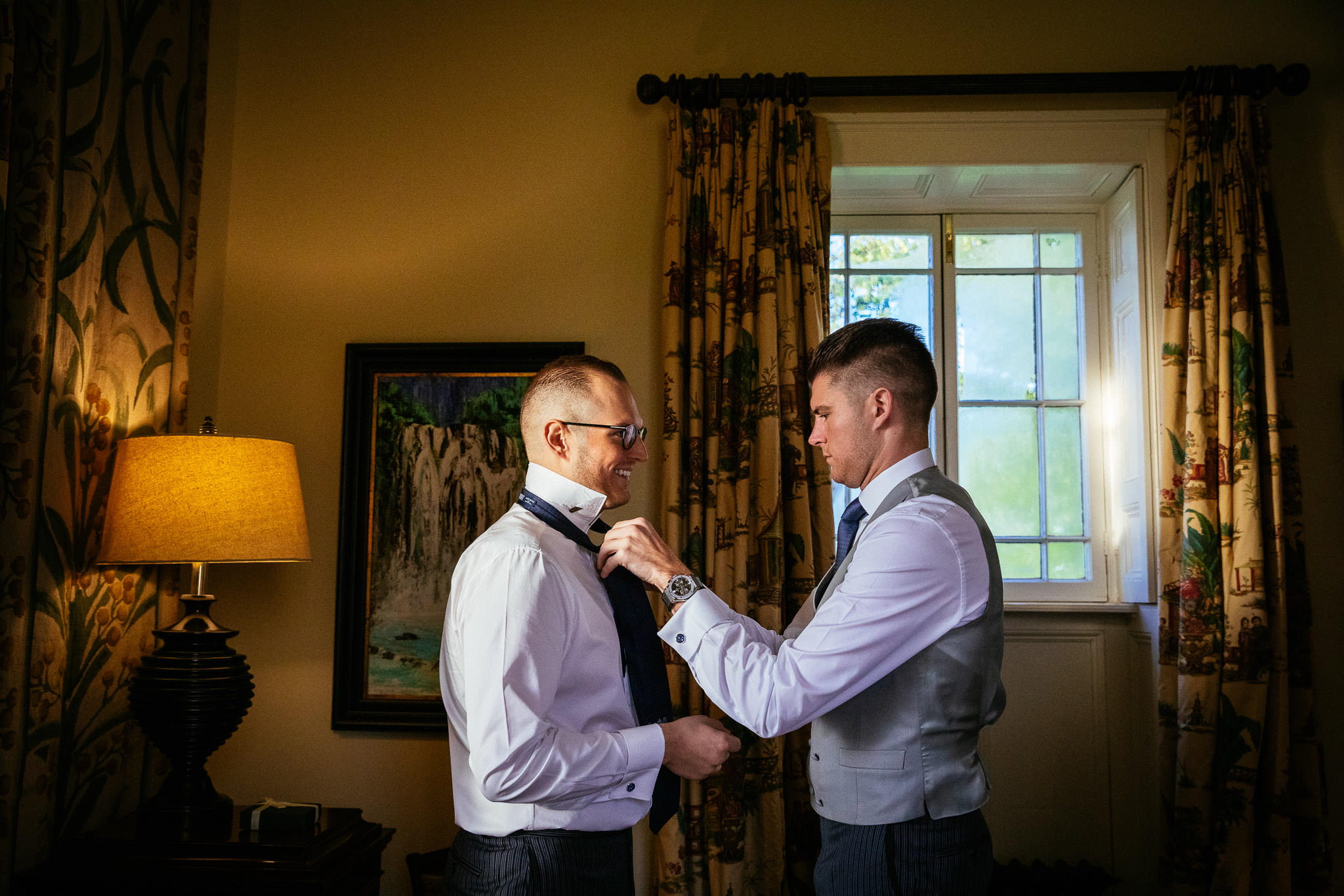 groomsman helping groom with tie at loughcrew lodge wedding