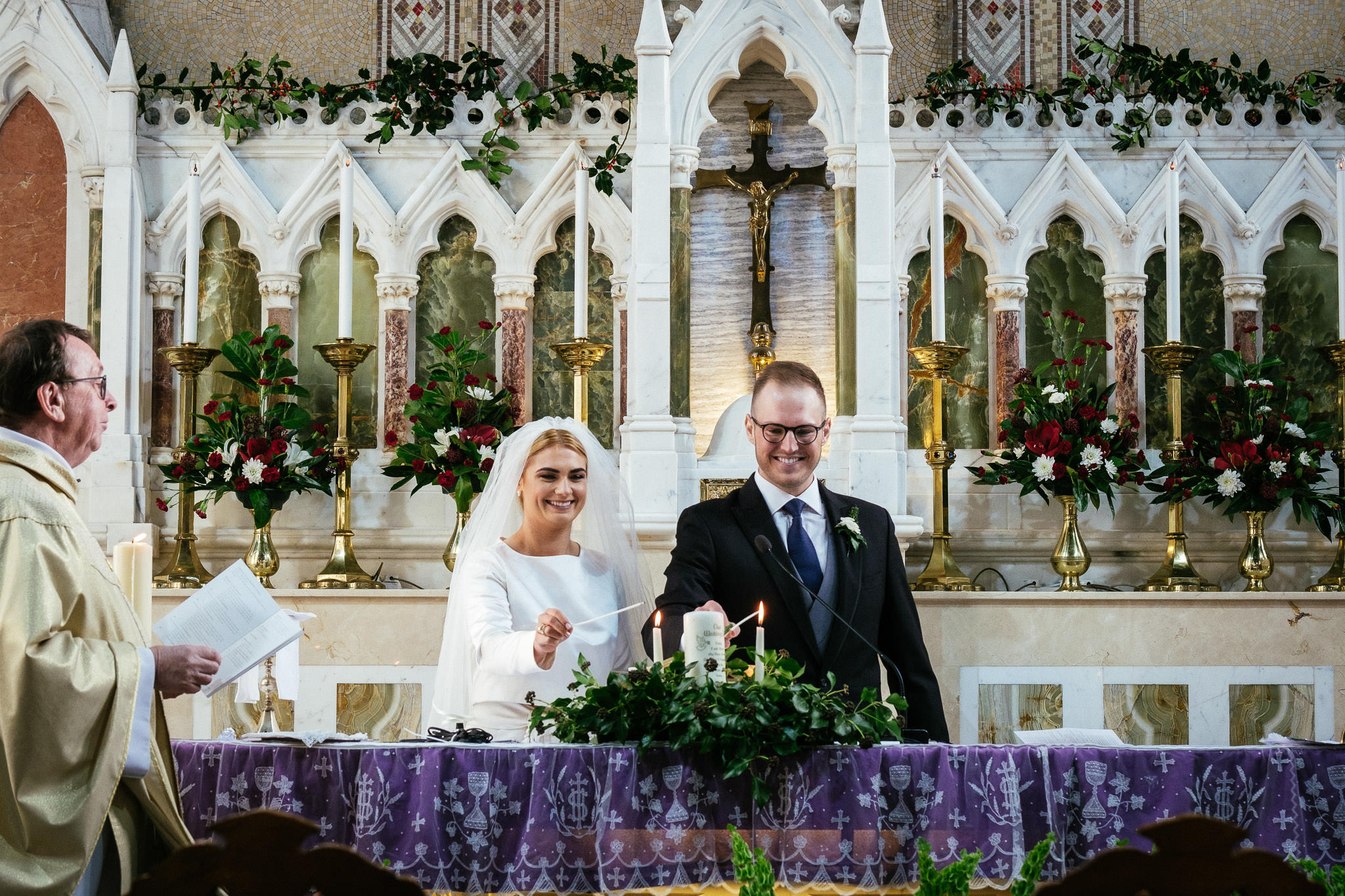 bride and groom lighting candles during wedding ceremony at St Brigid's Church Oldcastle