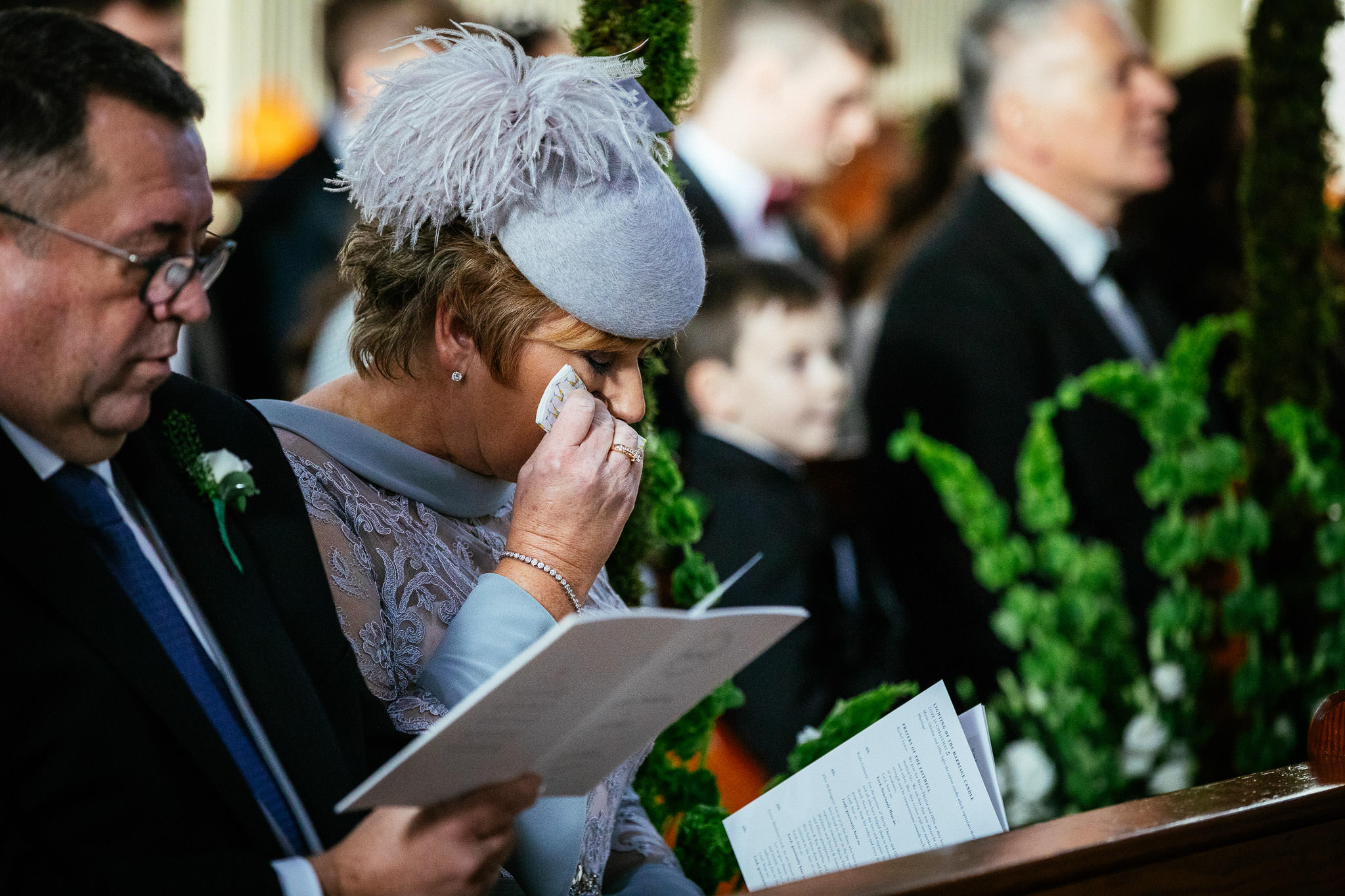 mother of groom wiping a tear during wedding ceremony at St Brigid's Church Oldcastle