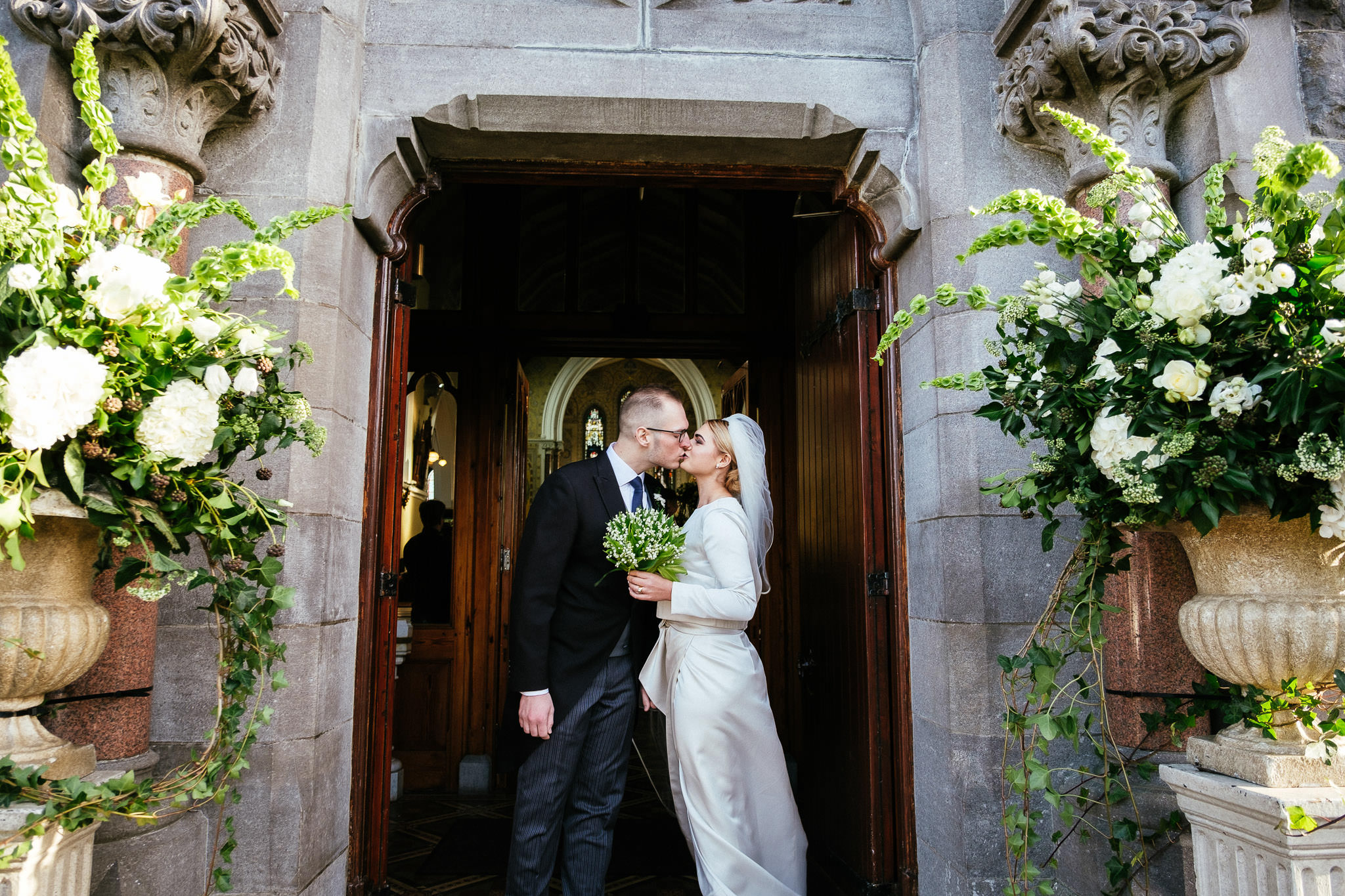 bride and groom kissing at church door after their wedding ceremony at St Brigid's Church Oldcastle
