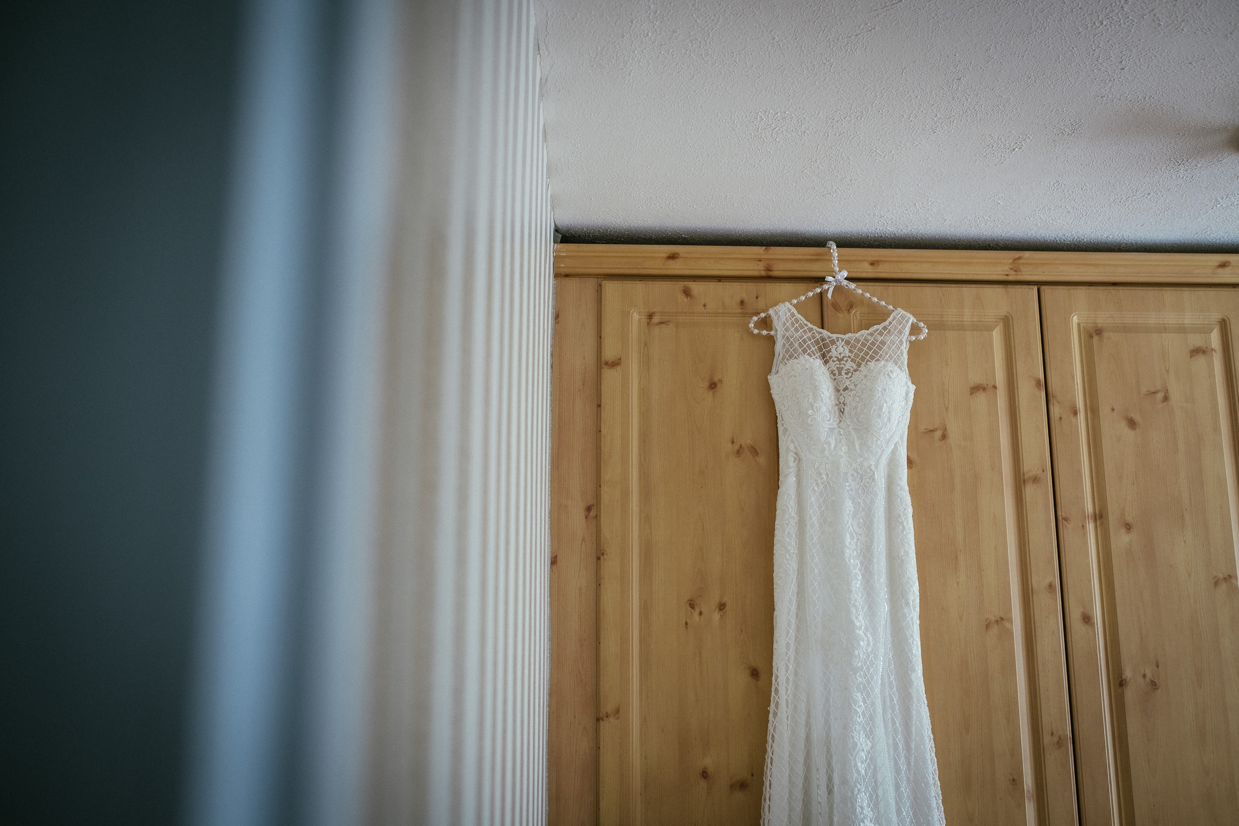 wedding dress hanging by wardrobe