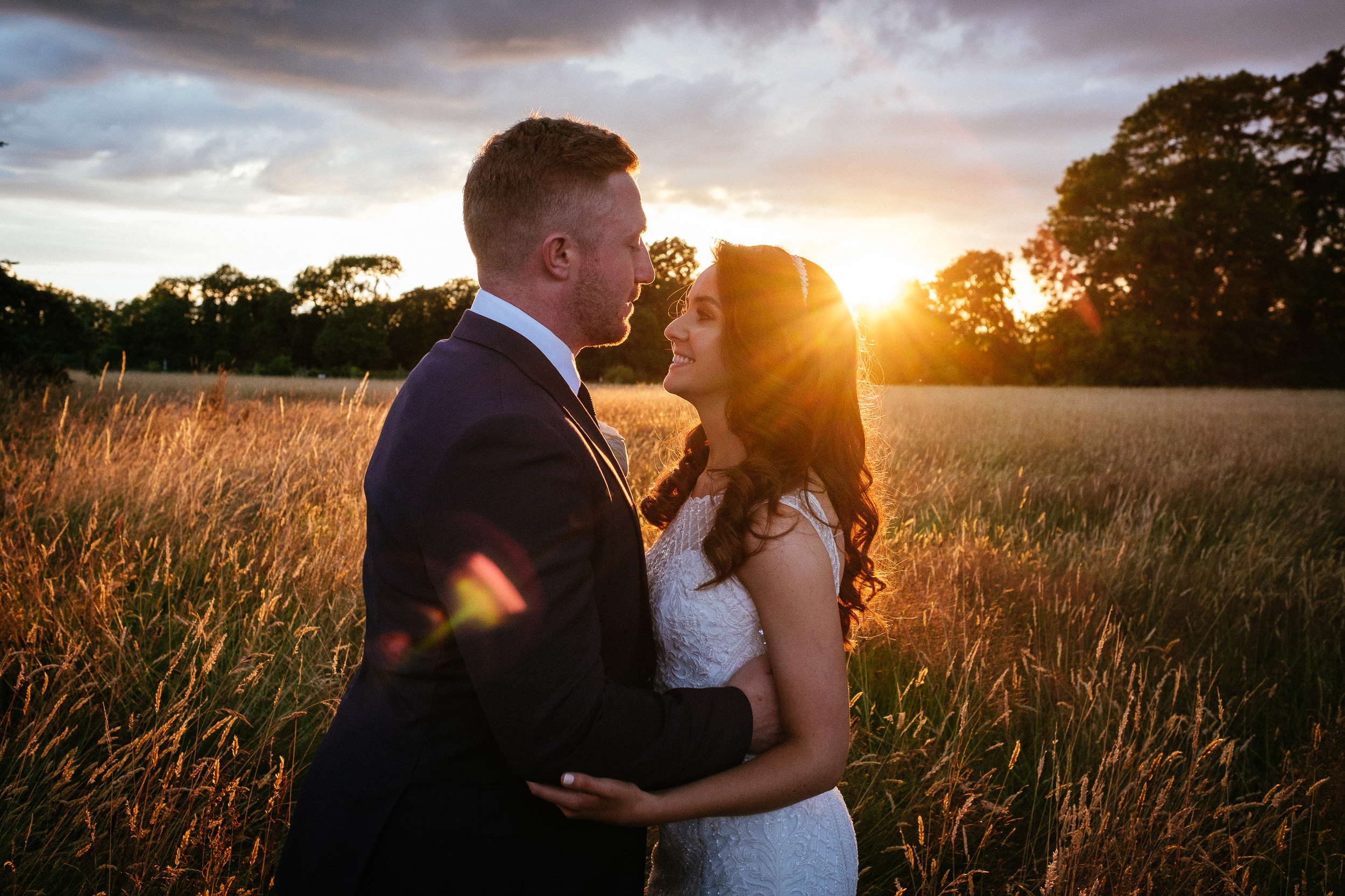 bride and groom standing in a field with an amazing sunset at their killashee house hotel wedding
