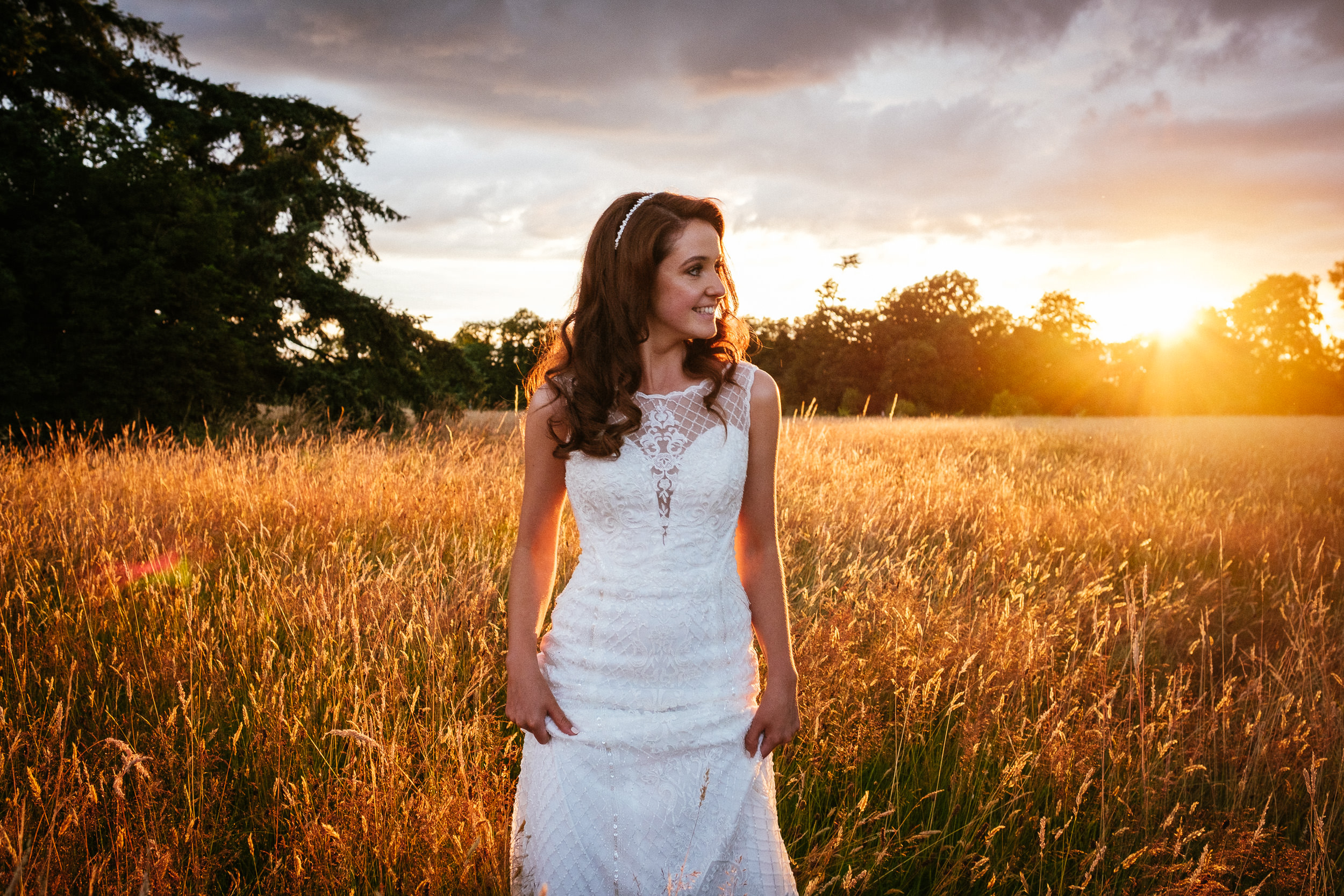 bride standing laughing in a field with an amazing sunset behind her at her killashee house hotel wedding