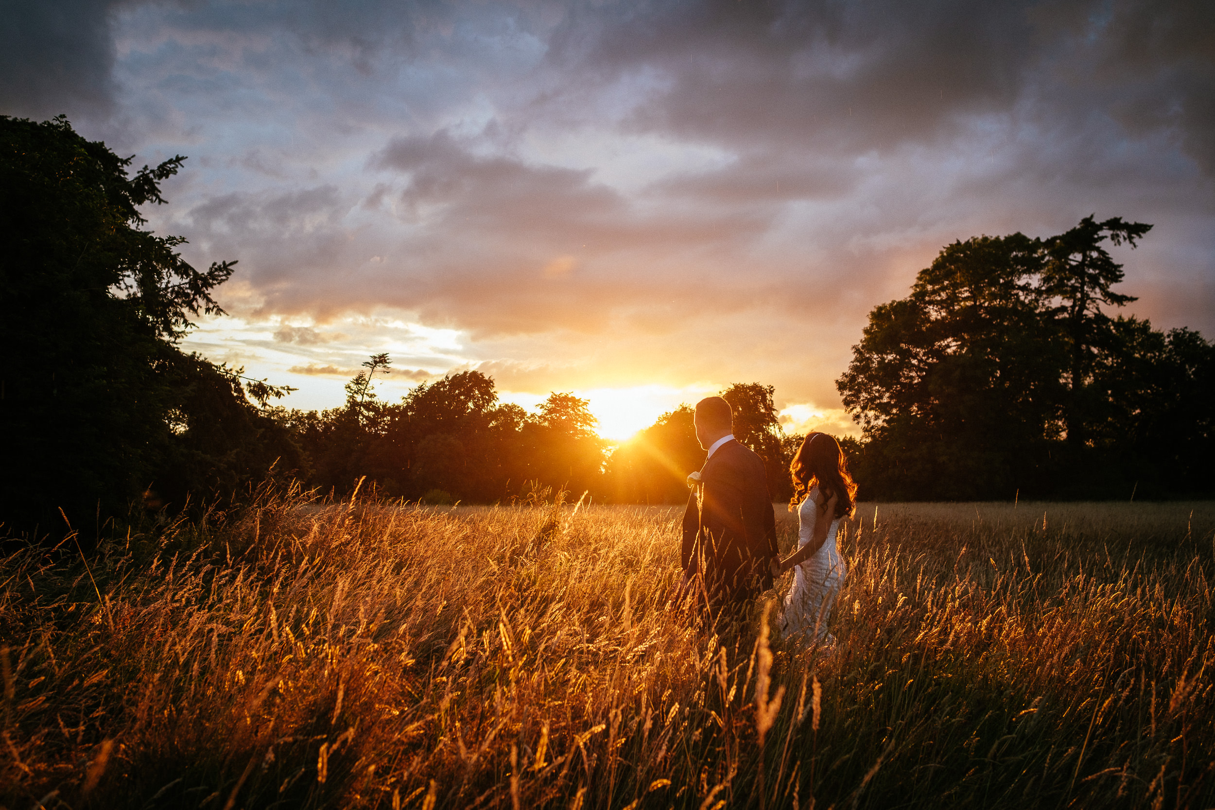 bride and groom strolling through a field of wheat towards an amazing sunset at their killashee house hotel wedding