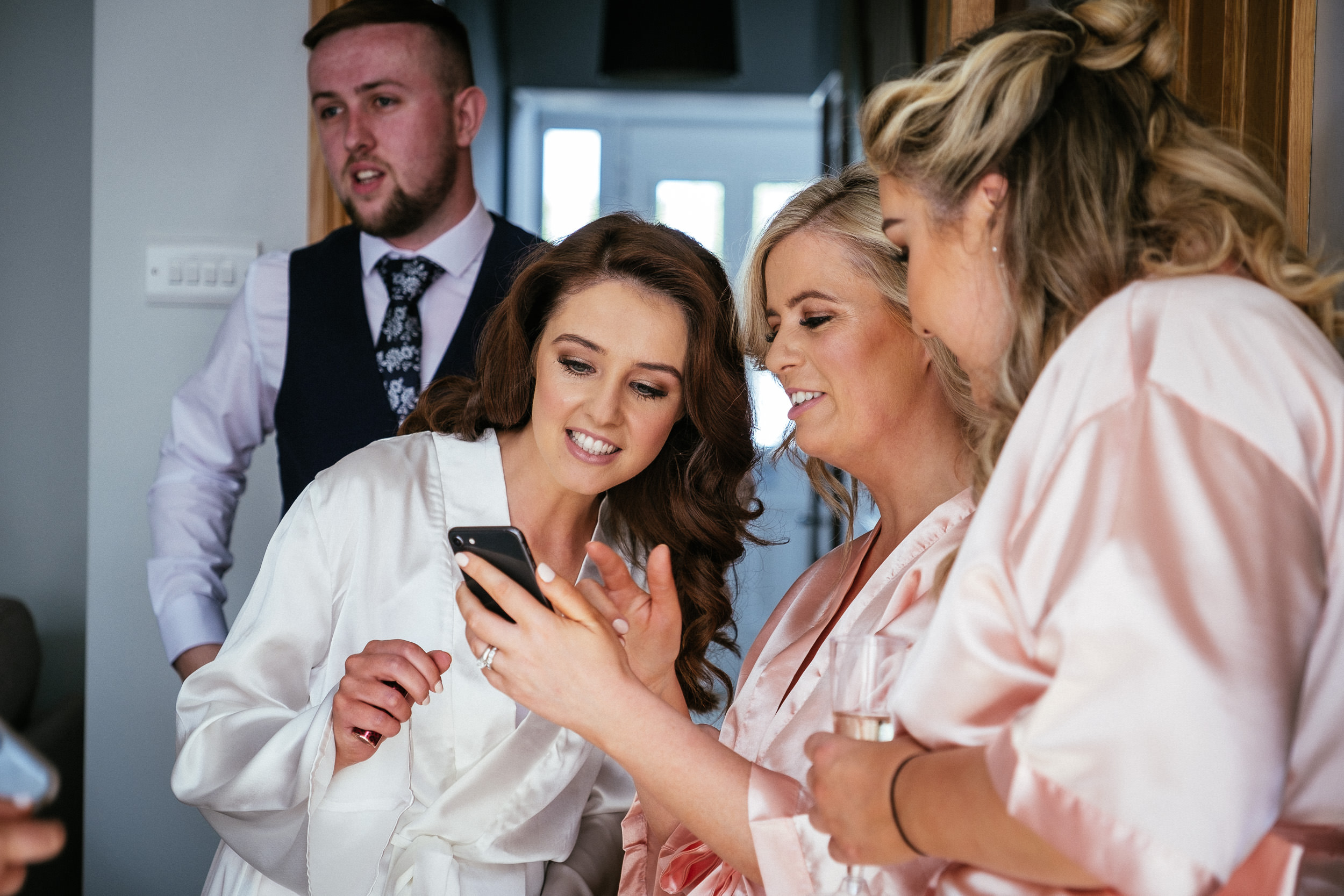 bride looking at phone and laughing before her killashee house hotel wedding
