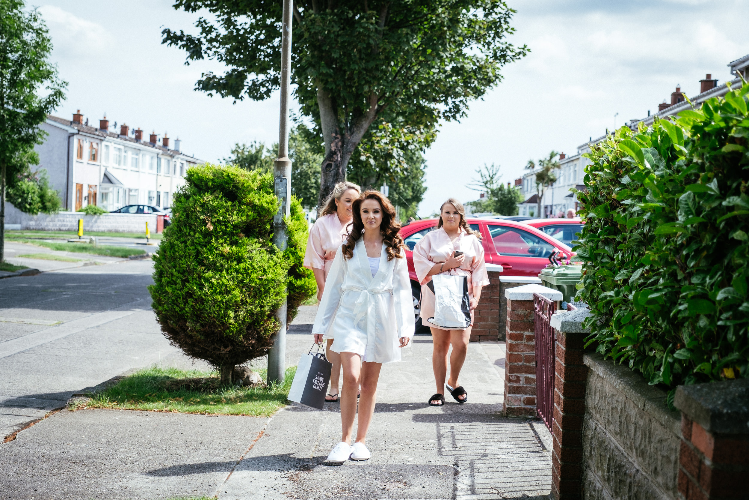 bride and bridesmaids walking down Dublin street wearing dressing gowns