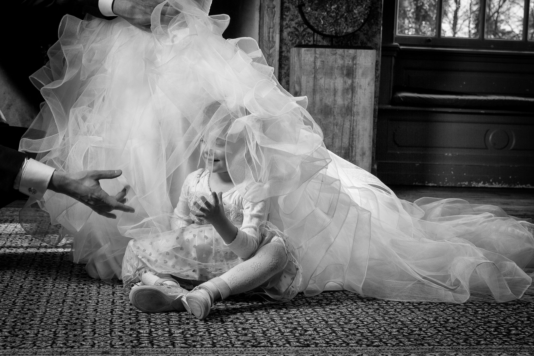 little girl playing with brides veil