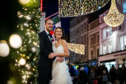 bride and groom embracing and laughing on grafton street in dublin at their christmas wedding