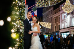 bride and groom on Grafton street at night under christmas lights