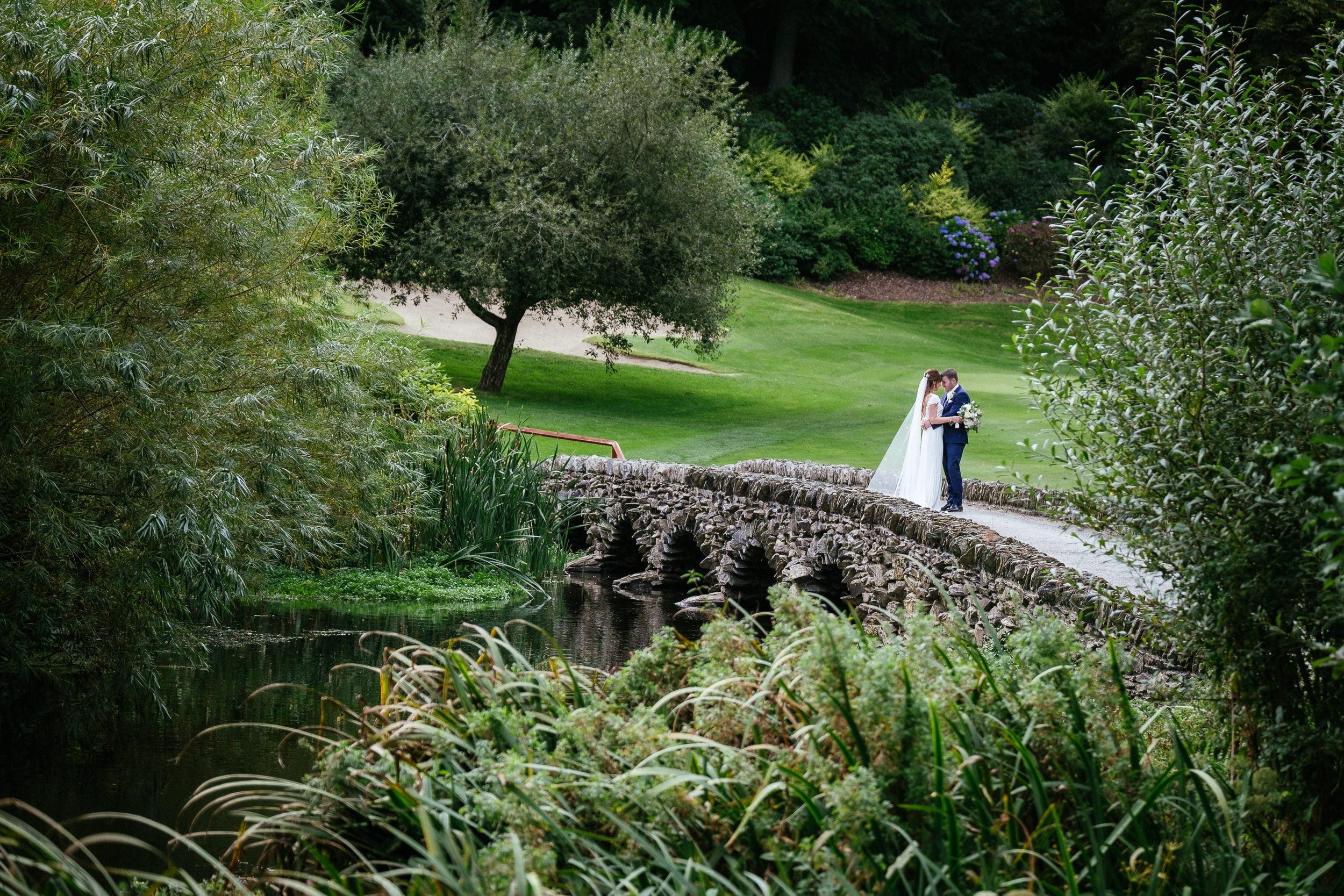 bride and groom on bridge at wedding in Druid's Glen Hotel Wicklow