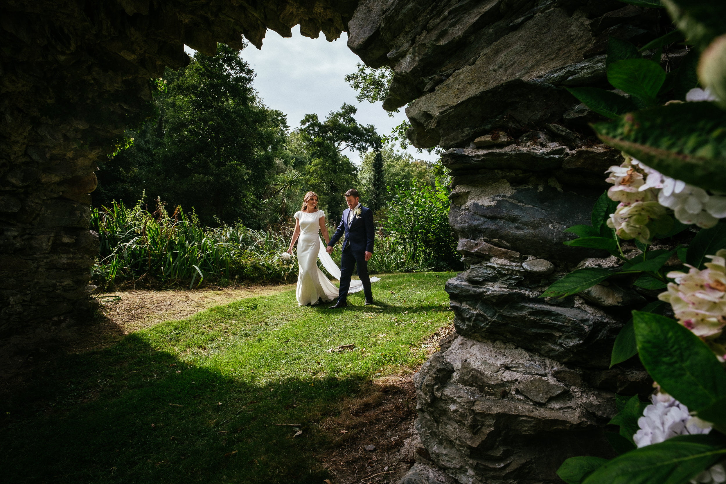 bride and groom walking through arch at wedding in Druids Glen Hotel Wicklow