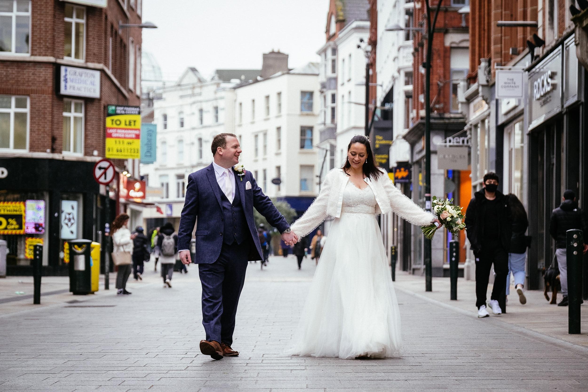 bride and groom walking down Grafton Street to their City Hall Dublin wedding