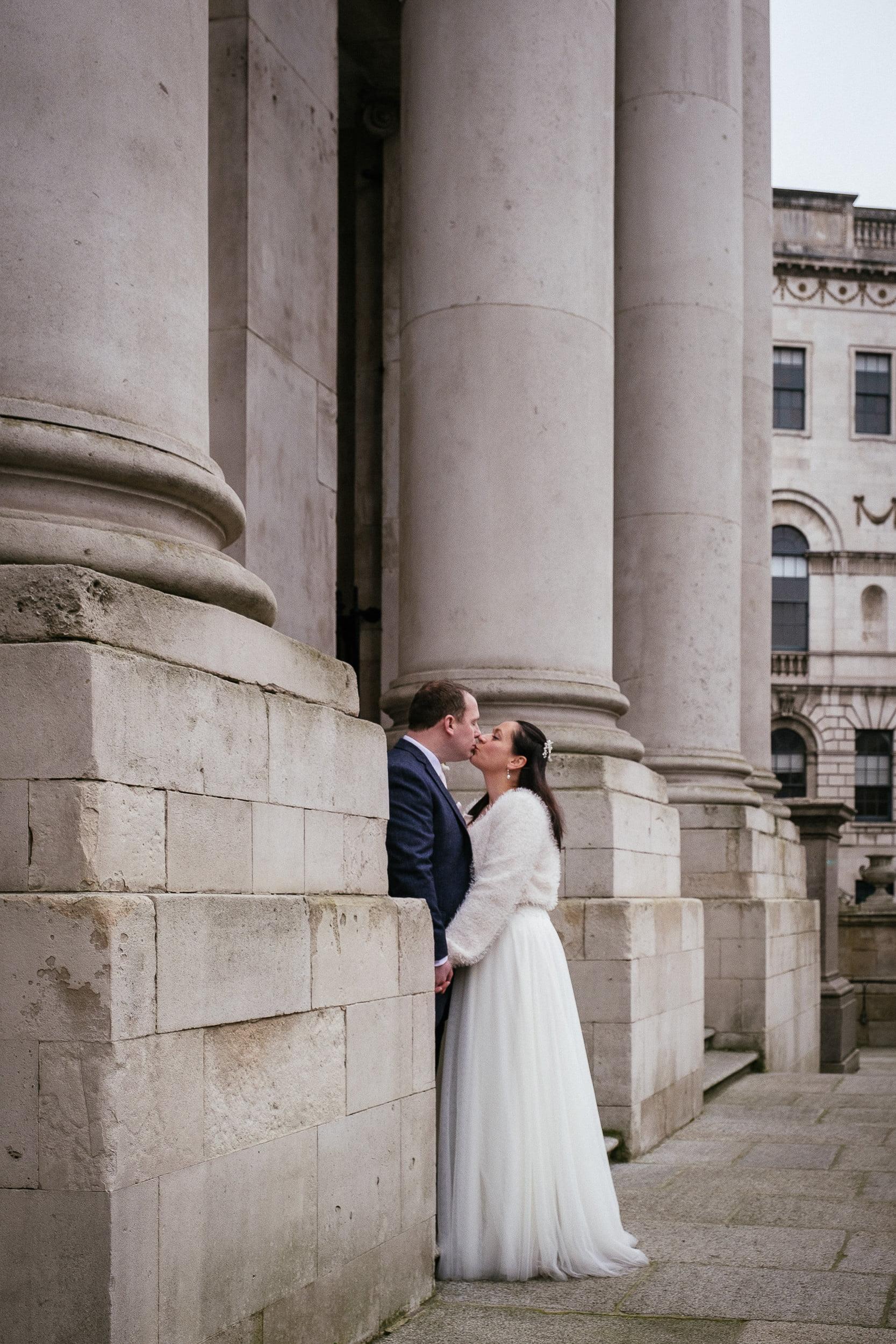 bride and groom kissing outside City Hall Dublin wedding