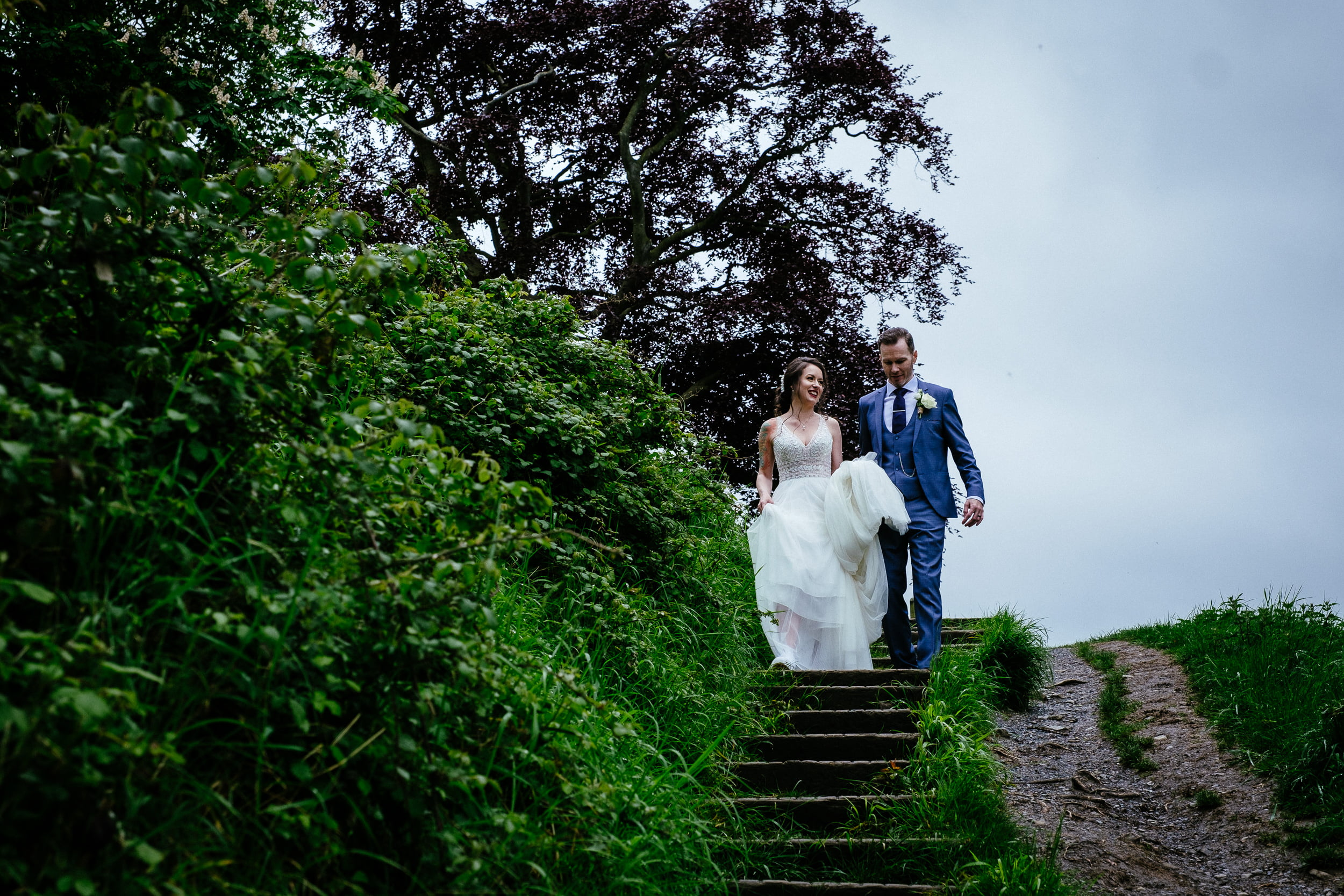 bride and groom walking down steps into the furry glen in the the phoenix park in dublin